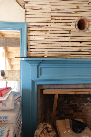 The rear floor parlor undergoing restoration. Paint analysis revealed this deep blue was the original color for one of the parlor mantels.