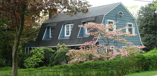 Gambrel roofed Colonial, or Arts & Crafts cottage? Bracketed by a pink flowering dogwood and a mature beech tree, this house at 37 Circle Road adjacent to No. 85 sports window shutters with a unique cutout typical of the whimsical details favored by Arts & Crafts era designers.