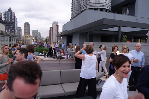 Speed Dating?: The DUMBO rooftop is a whirl of motion as my classmates move from one to another catching up. Spouses were invited and several joined the revelry. Our host's husband even cooked the Columbians hot dogs.