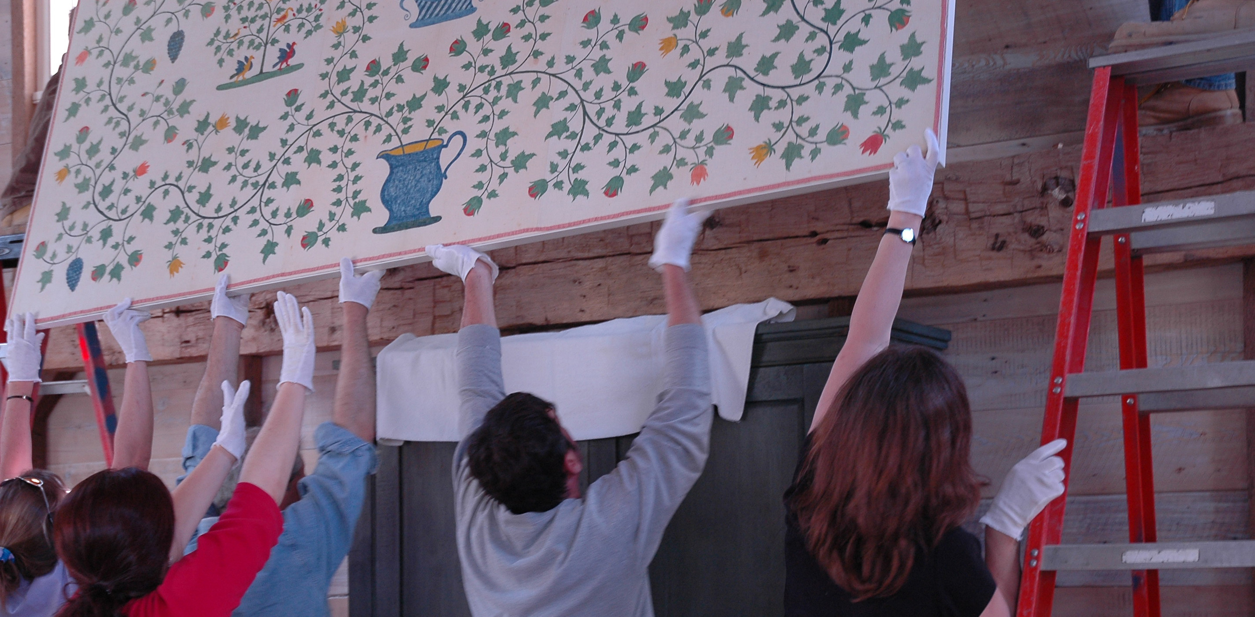Conservators are assisted by art handlers as they hoist a large-mounted quilt onto its exhibition space.
