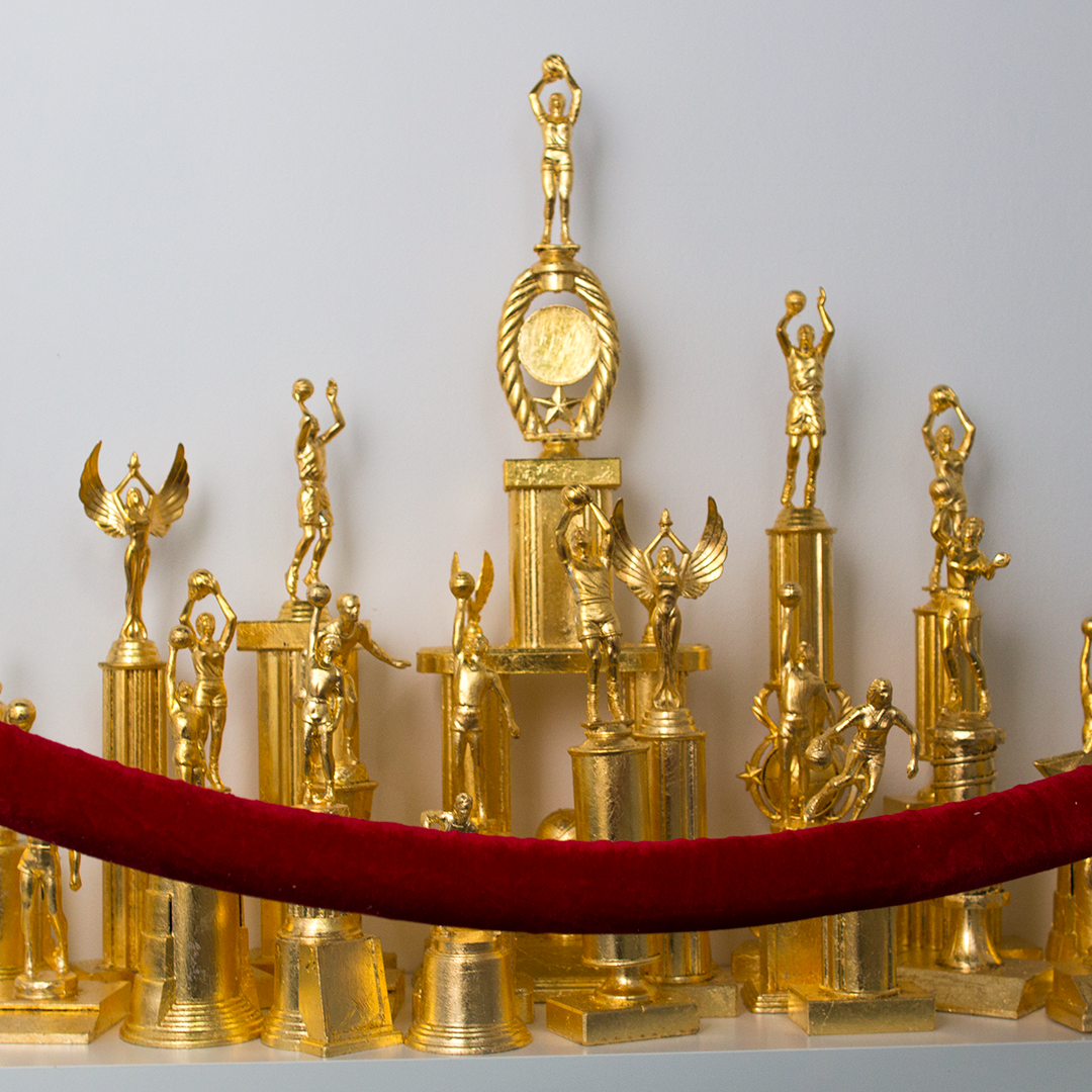 "Victor Solomon, ""Roll with the winners."" 2016. 22 gilded trophies installation, 36 x 24 in."