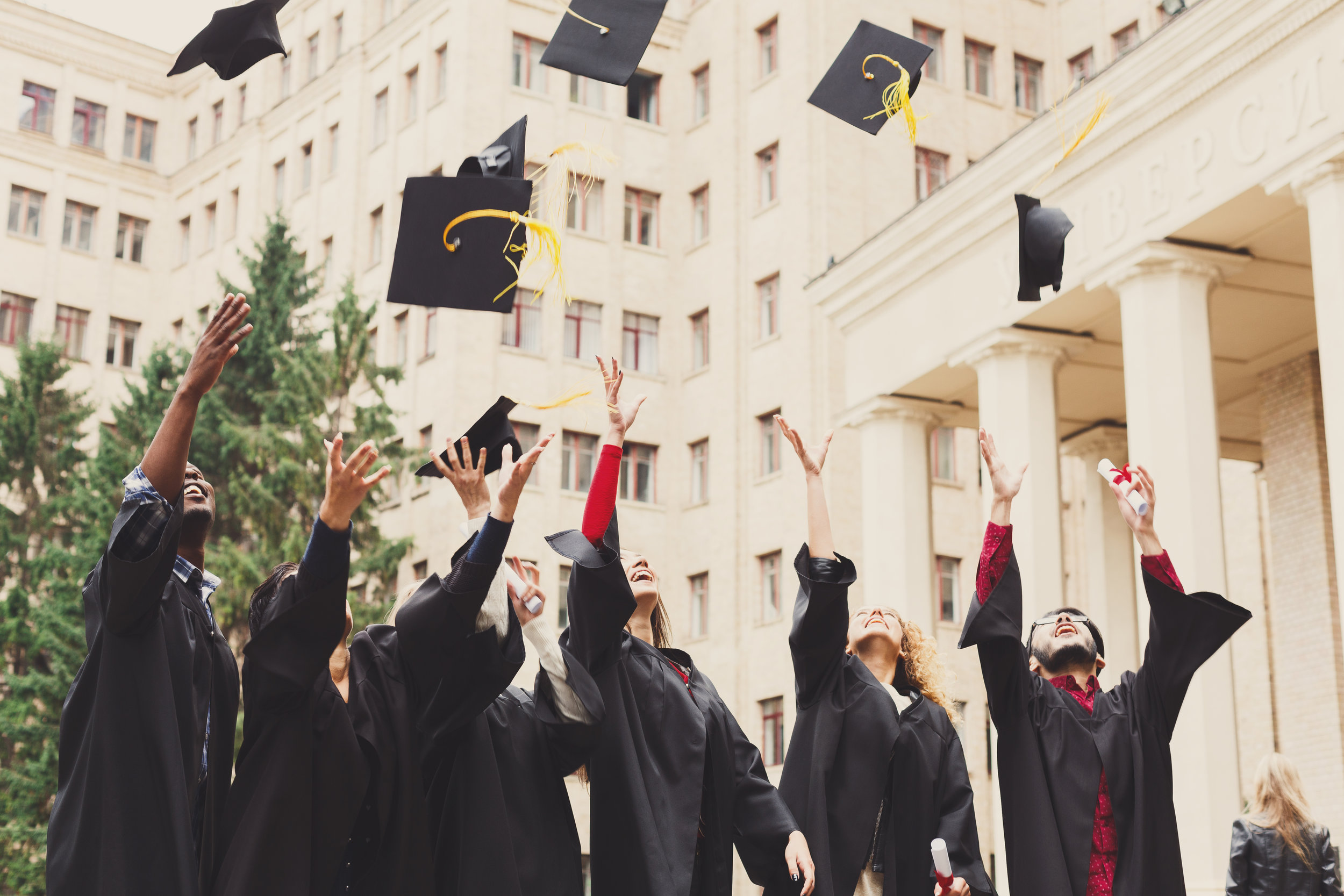a-group-of-graduates-throwing-graduation-caps-in-72VH46X.jpg