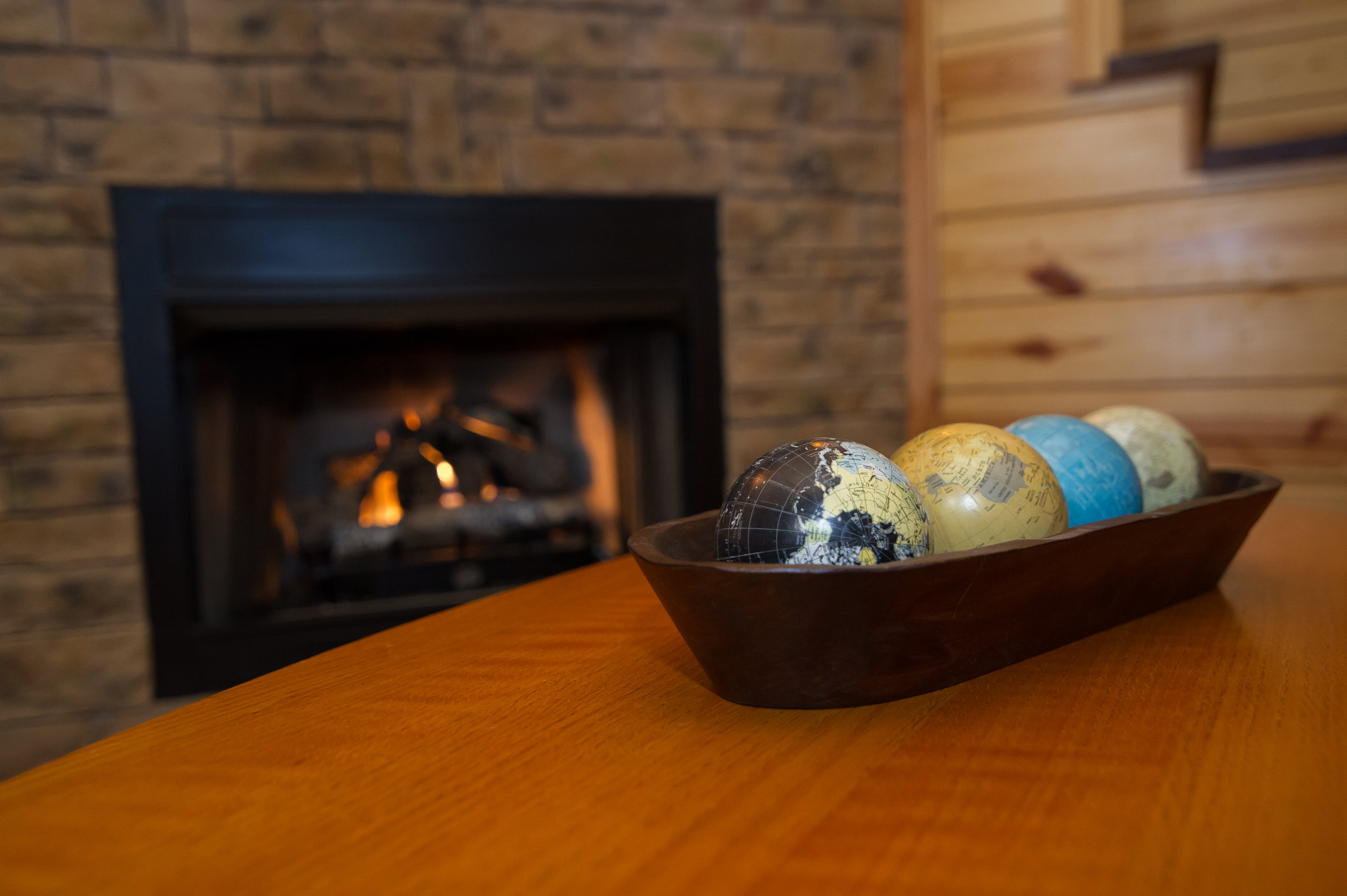 Wood dish of Globes and fireplace in background.jpg.jpg