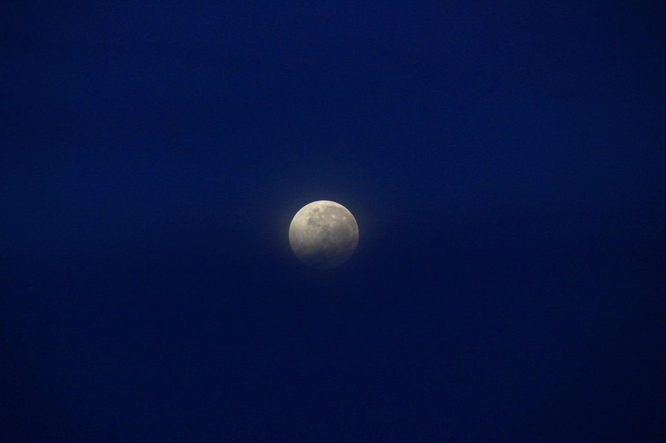 The super moon setting behind the volcanic peak of Mount Batur.
