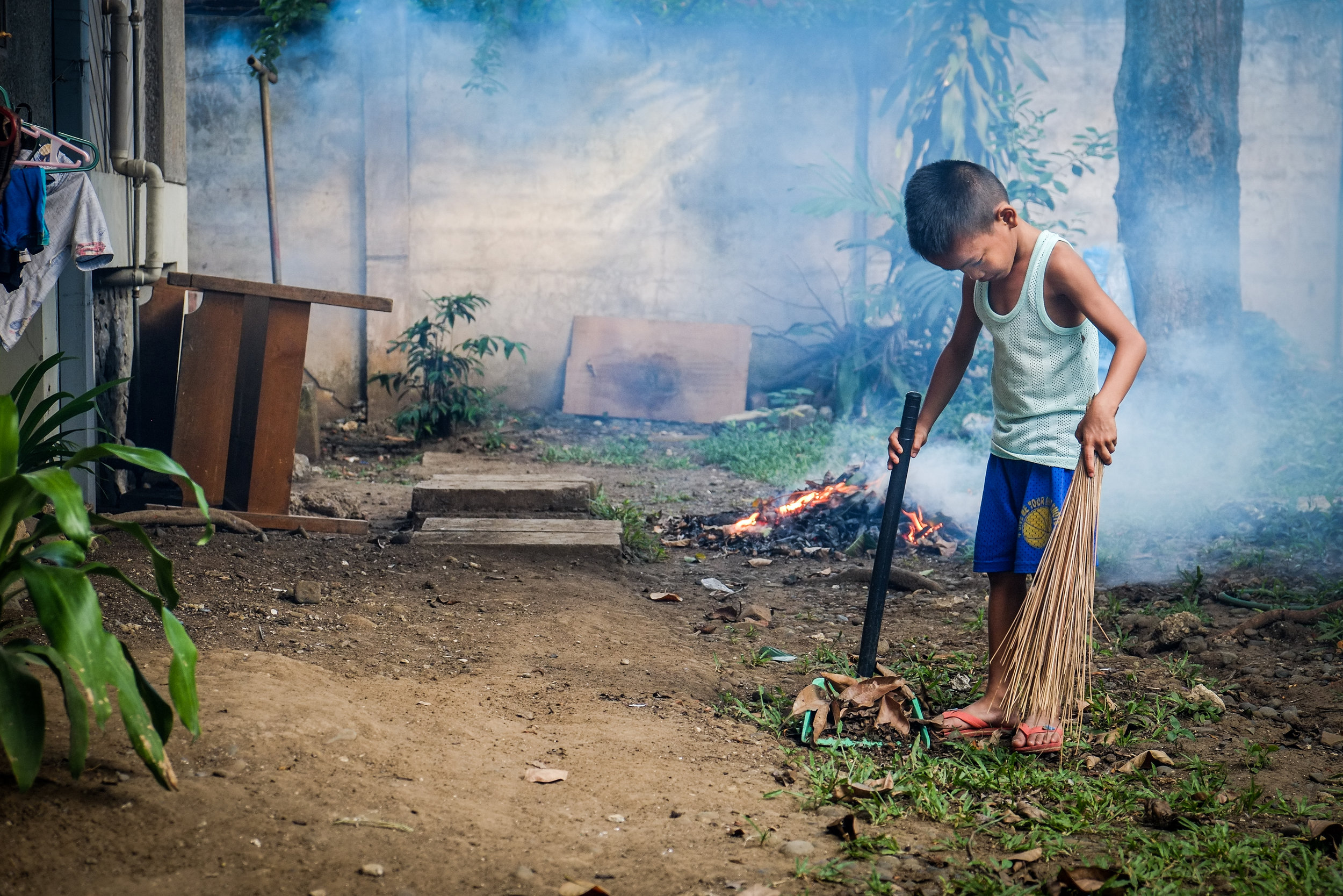 At SOS Davao a young boy performs his daily chores of sweeping up fallen leaves and burning them.