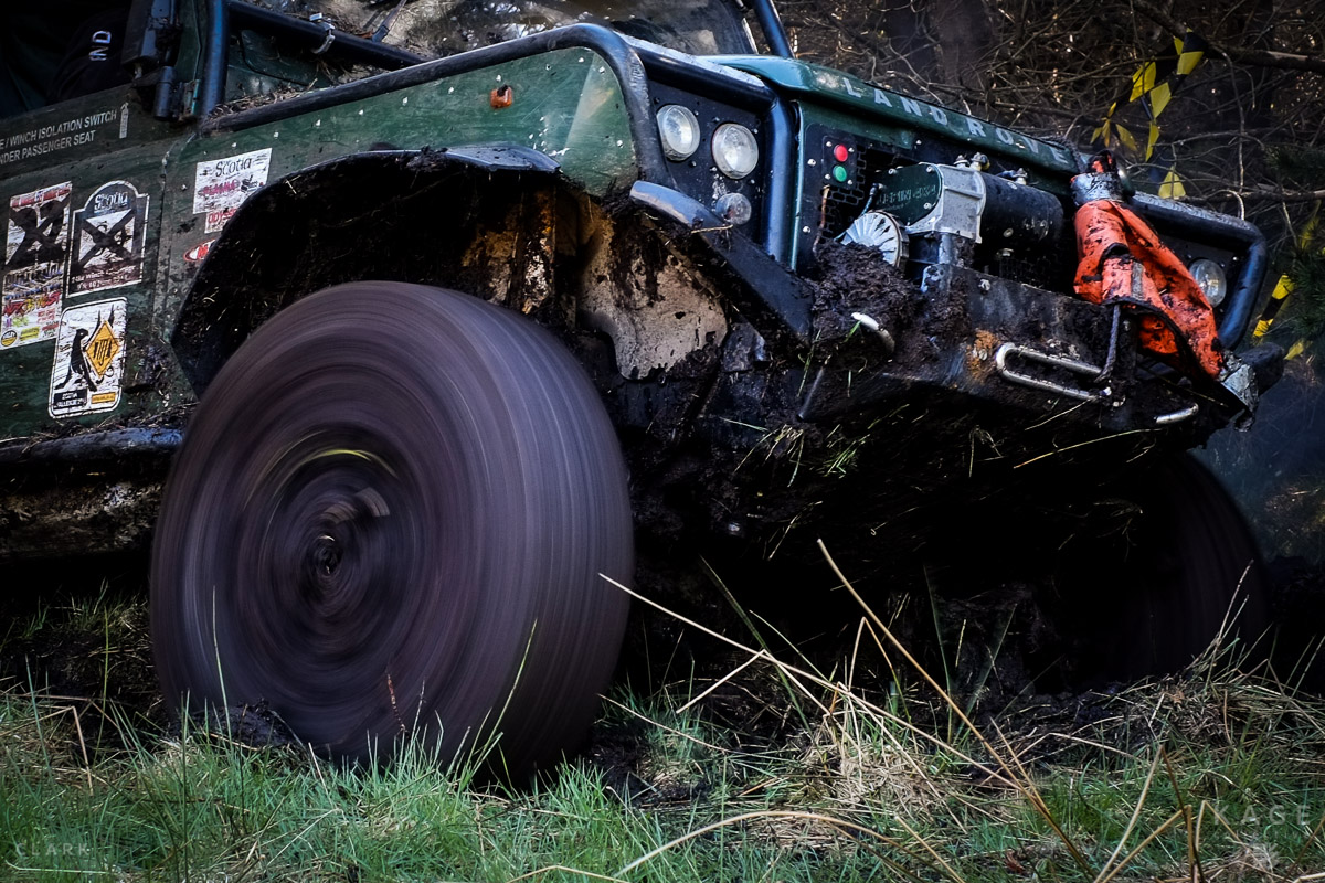 Wheels spin as the Land Rover attempts to pull itself out of a ditch.