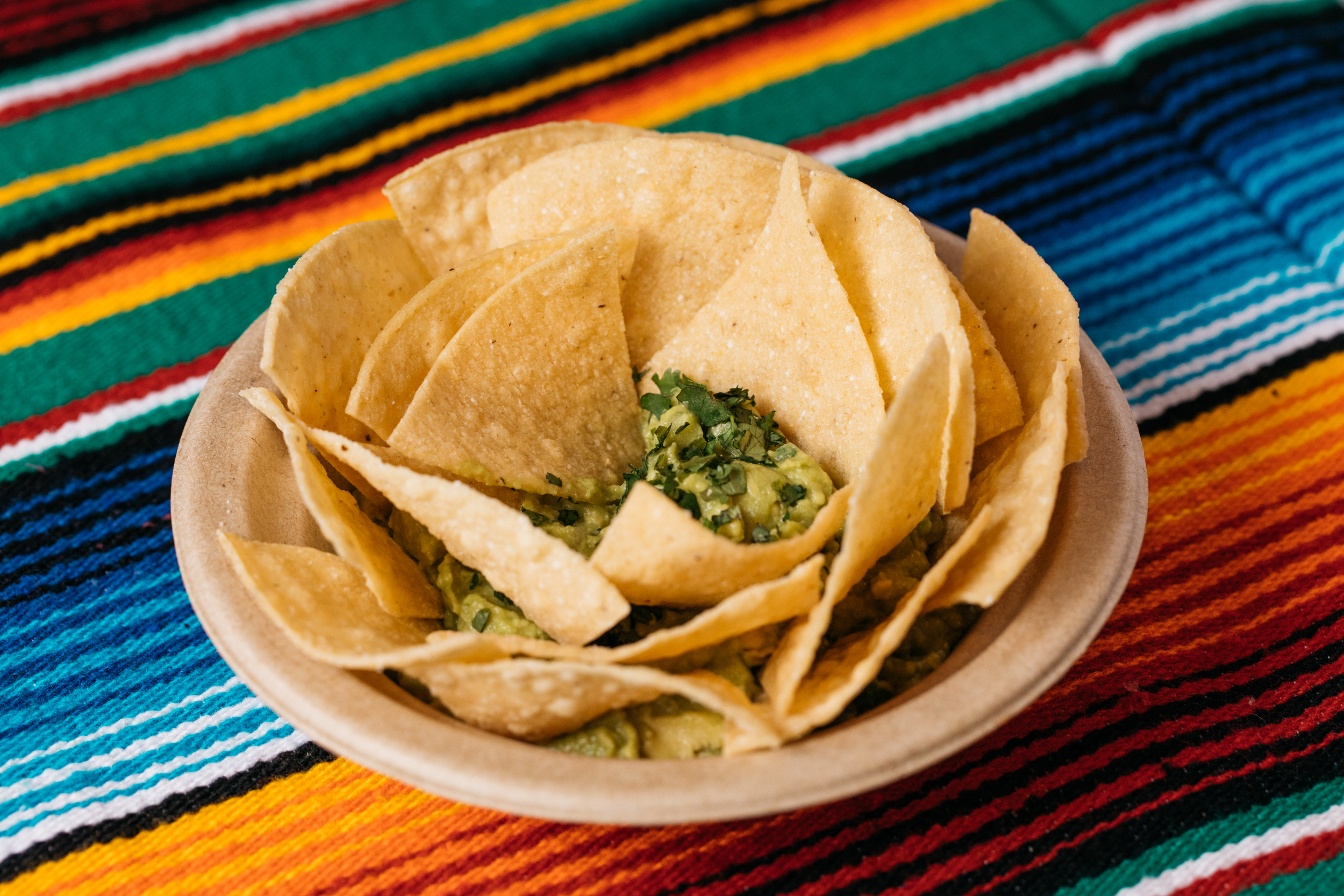 GUAC + CHIPS 8 - VEGAN + GLUTEN FREE. House chips. Avocado, onion, jalapeño, lime, cilantro.