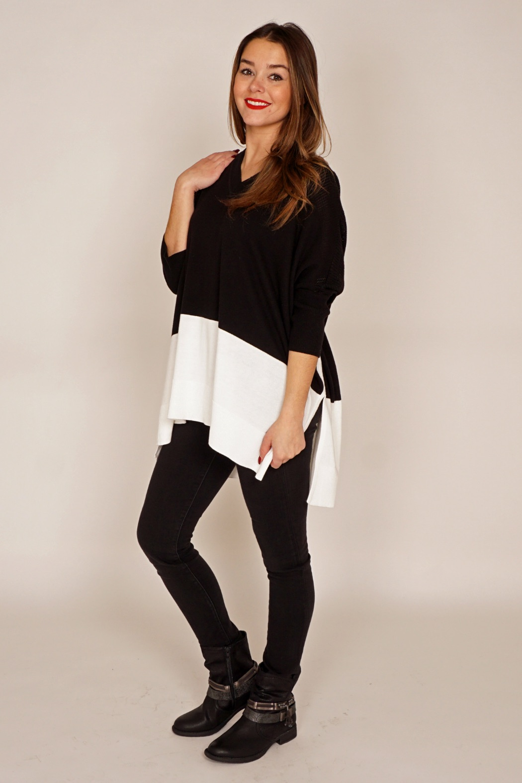 """Since the poncho's popularity is booming, it's time to take advantage of its benefits this season. The only rule necessary to keep in mind when wearing a poncho is that the large volume that it gives you on top must be offset by a slim/minimalist style on the bottom. The poncho is popular simply because it's so easy to wear. It goes with everything. One size fits all. It's never too tight. Season after season, ponchos retain their """"go to"""" popularity in our wardrobes – from cool Summer nights to the coldest days in December. They make the perfect in-between-days outerwear when it's just a little too warm to wear a coat. Juanita actually finds it warmer than a fall coat as the arms are closer to the body and it seems more effective blocking the wind. She's been a poncho lover since her early 20's. It's also easier to layer, as it fits over bulkier sweaters, whereas it can be much more constricting trying to get that sweater into a coat."""