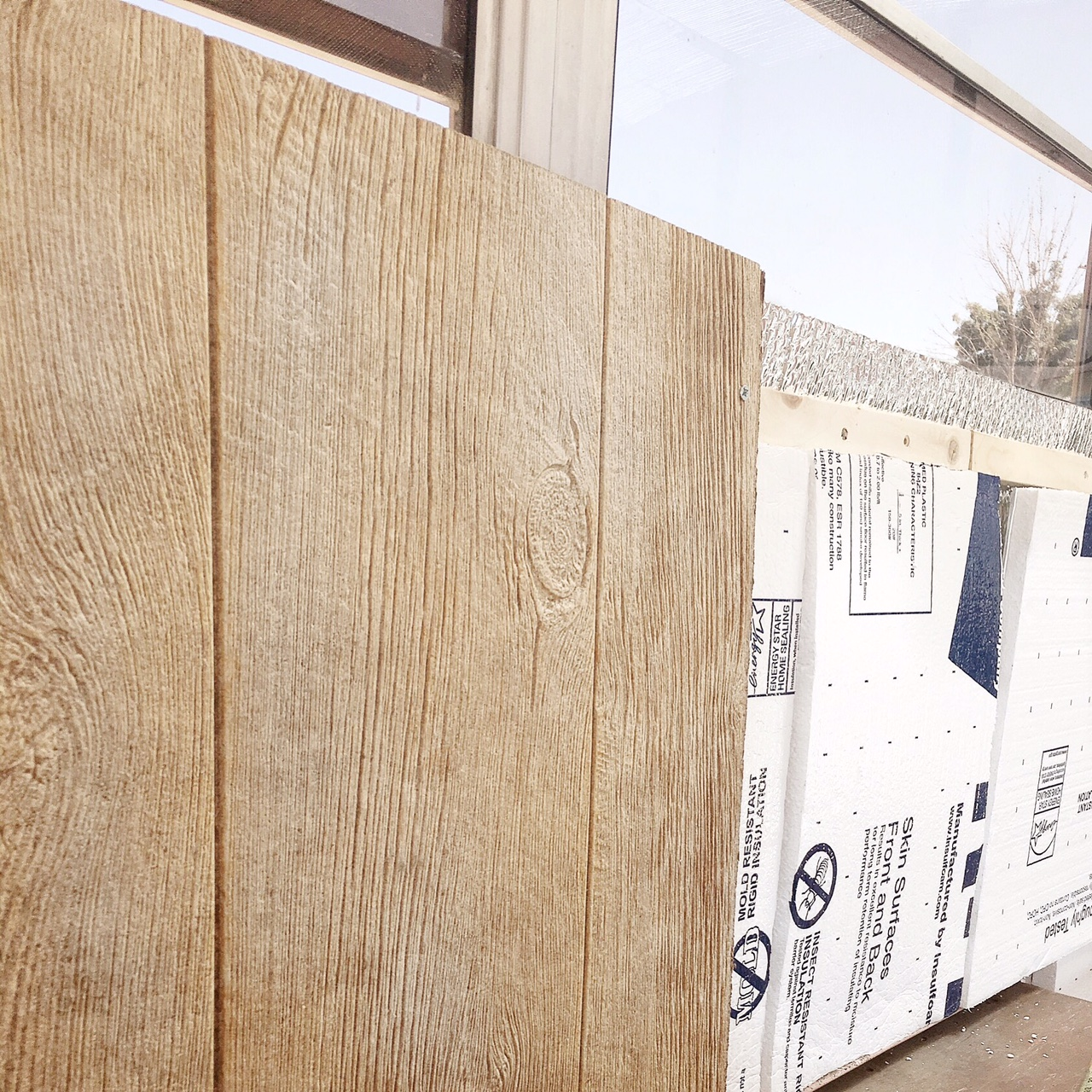 """Wood """"ribs"""", rigid foam insulation, and faux barn wood panels going up on the side walls."""