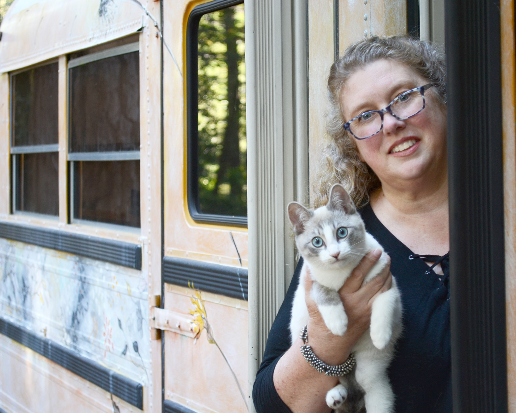 Jennifer Lorton with Furgus and Cozy the Bus, happily living the nomadic life ,  in the forest in Northern California.