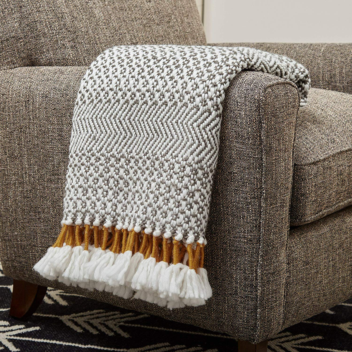 Hand woven  throw blanket  in shades of charcoal with mustard fringe.
