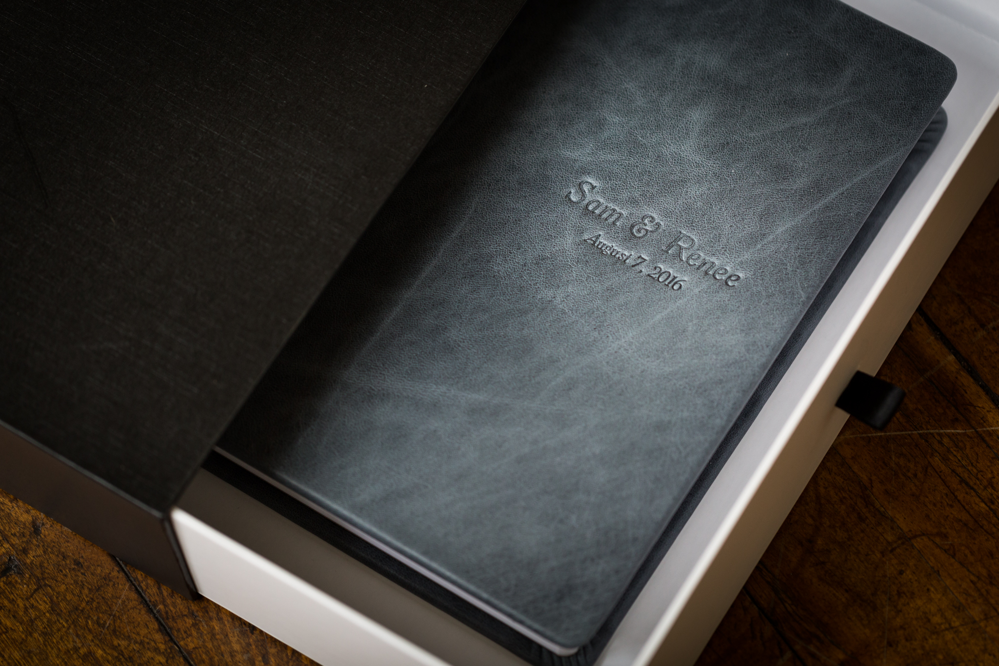 """A 10""""x10"""" genuine leather wedding album with the """"Rustic Denim"""" leather and custom debossing with complimentary slide box."""