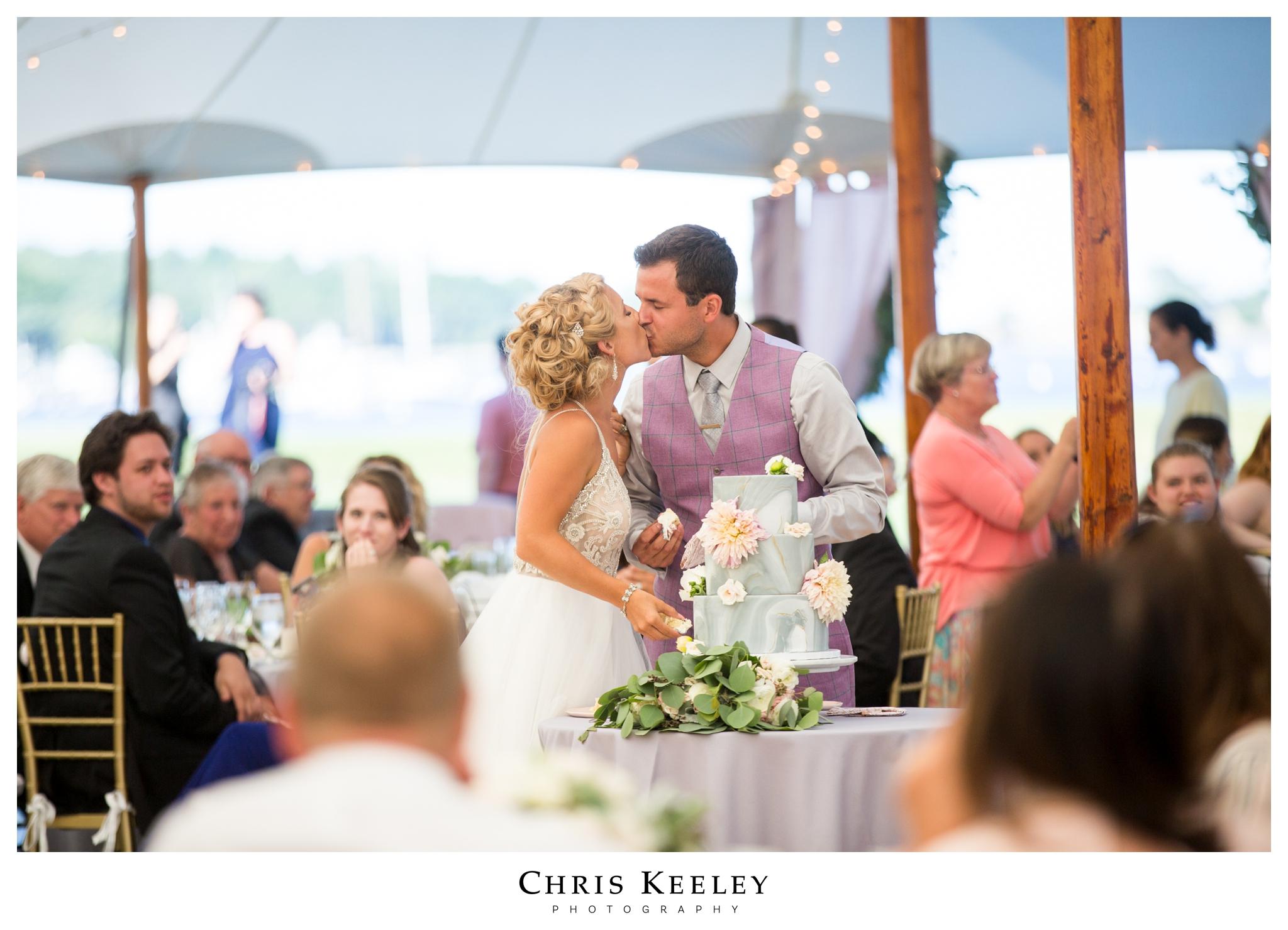 bride-groom-kiss-after-wedding-cake-cut.jpg