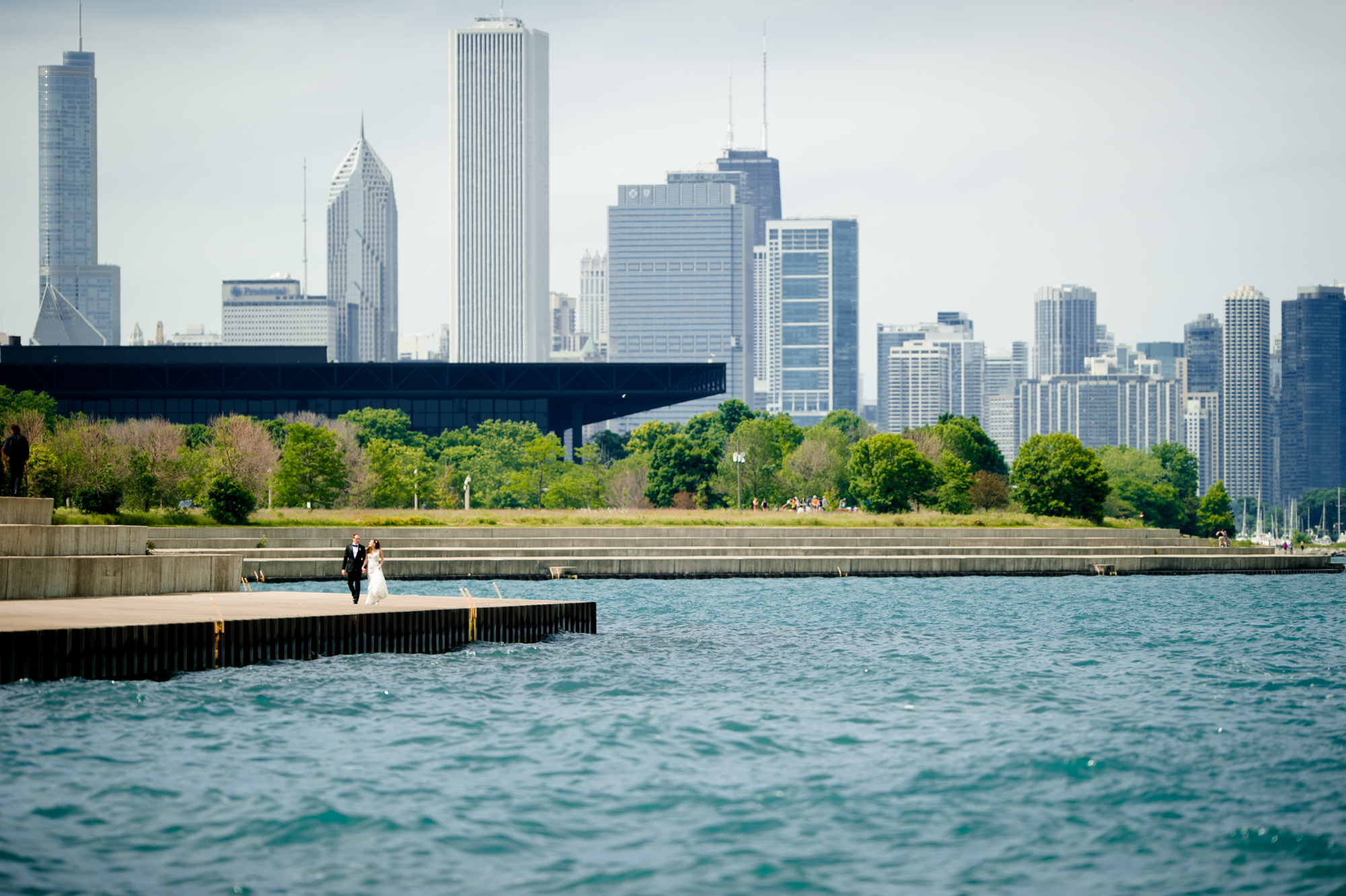 Fine art portrait of bride and groom against Chicago skyline