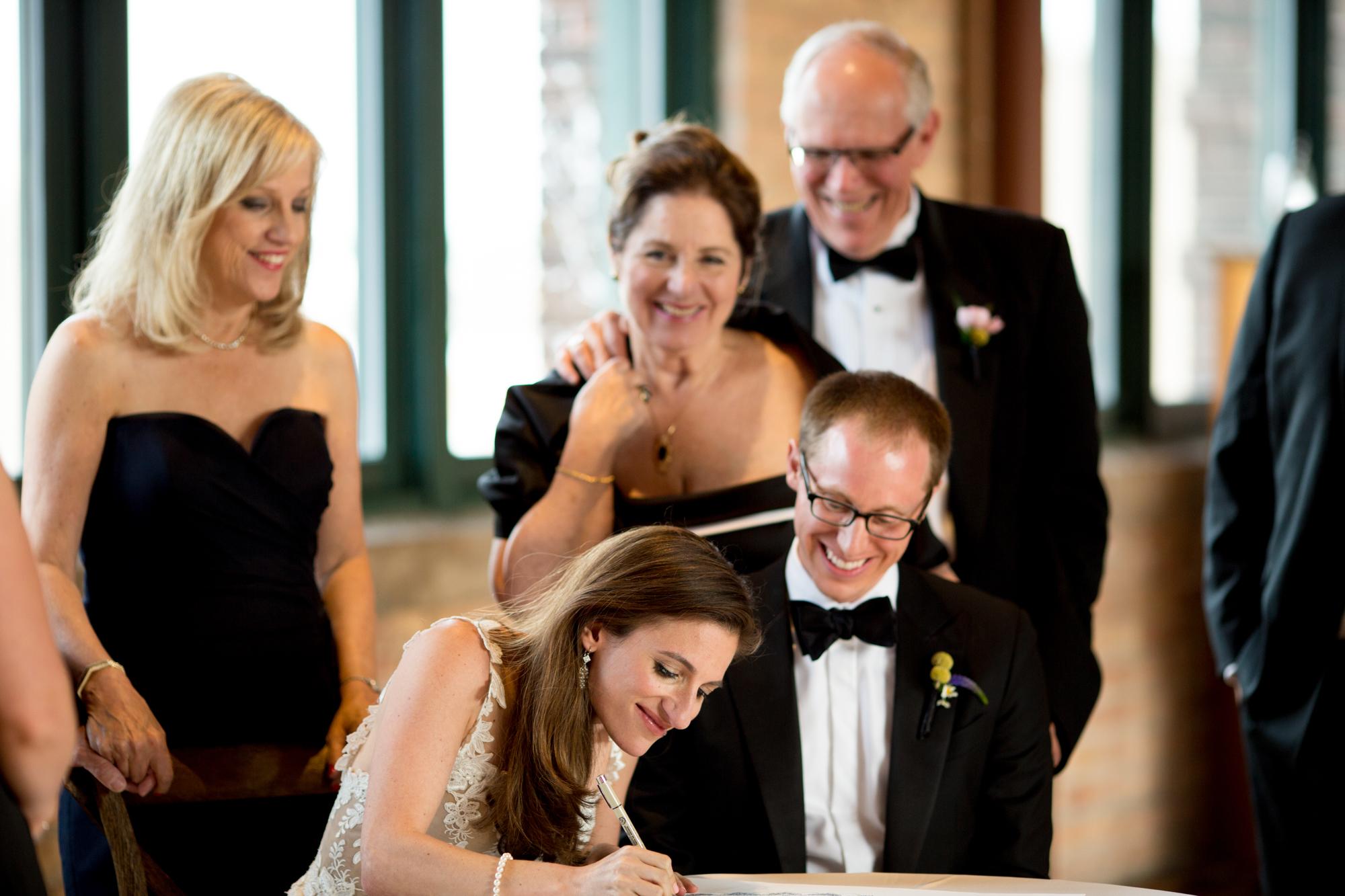 Bride and groom sign ketubah at Bridgeport Art Center