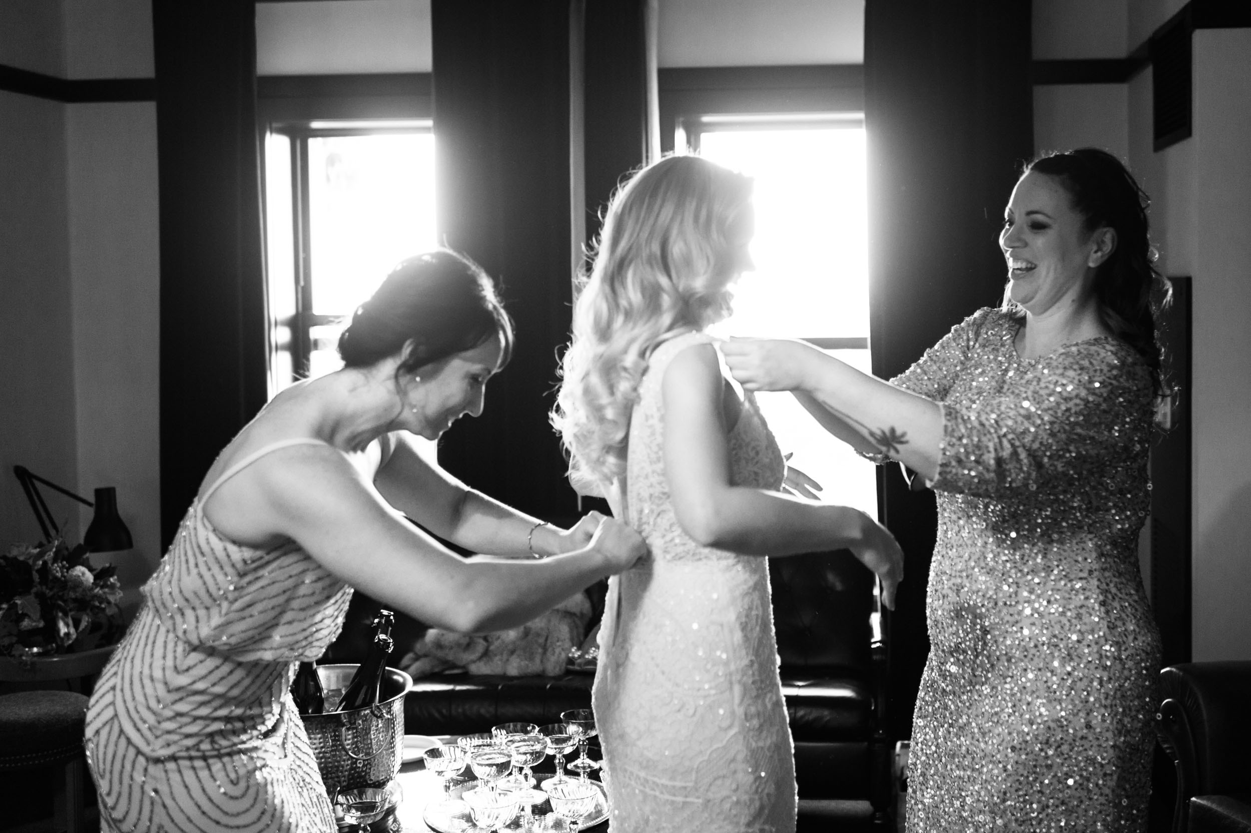 Bridesmaids help bride dress at Chicago Athletic Association Hotel