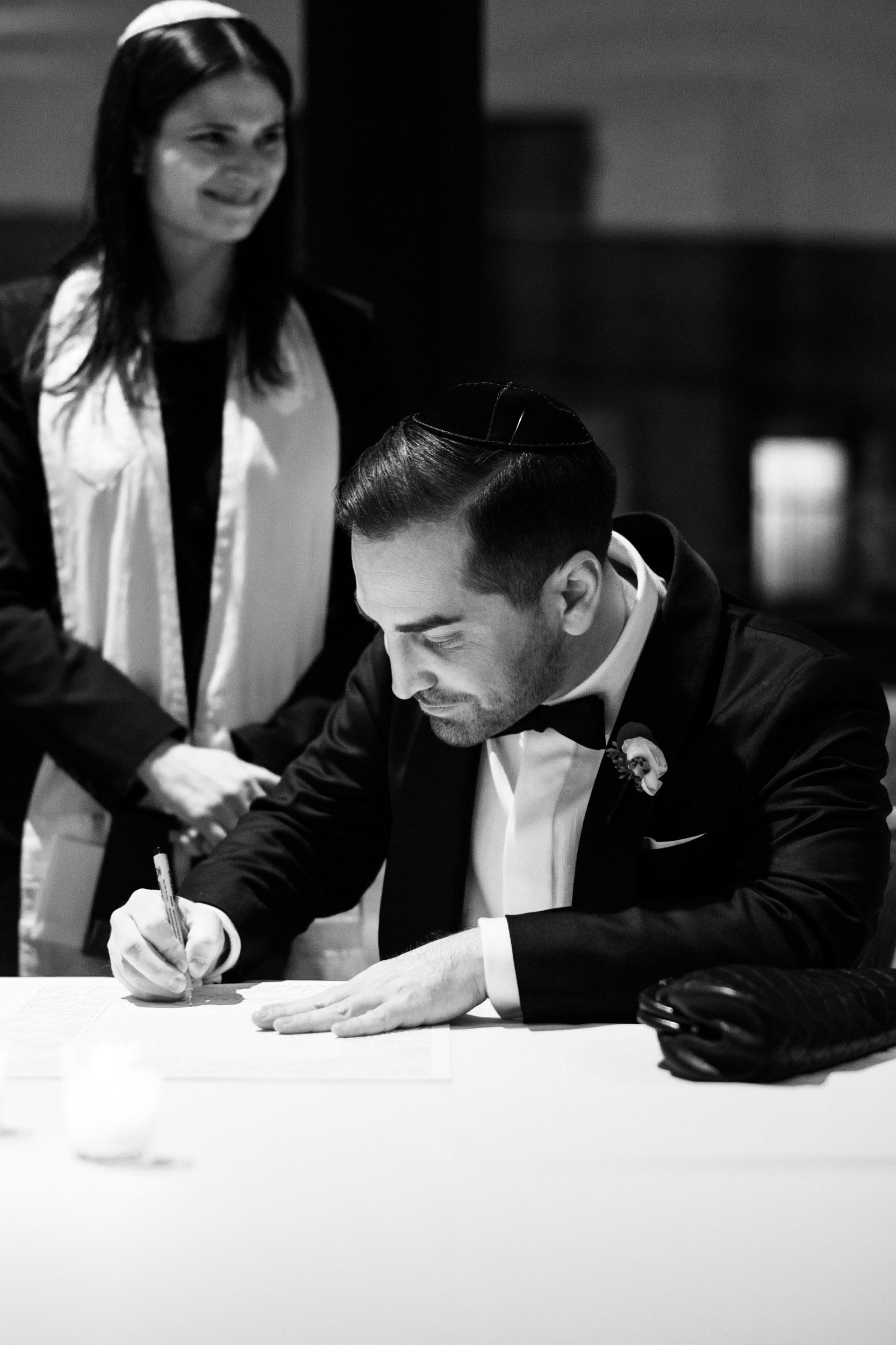 Groom signs the ketubah at Bridgeport Art Center wedding in Chicago