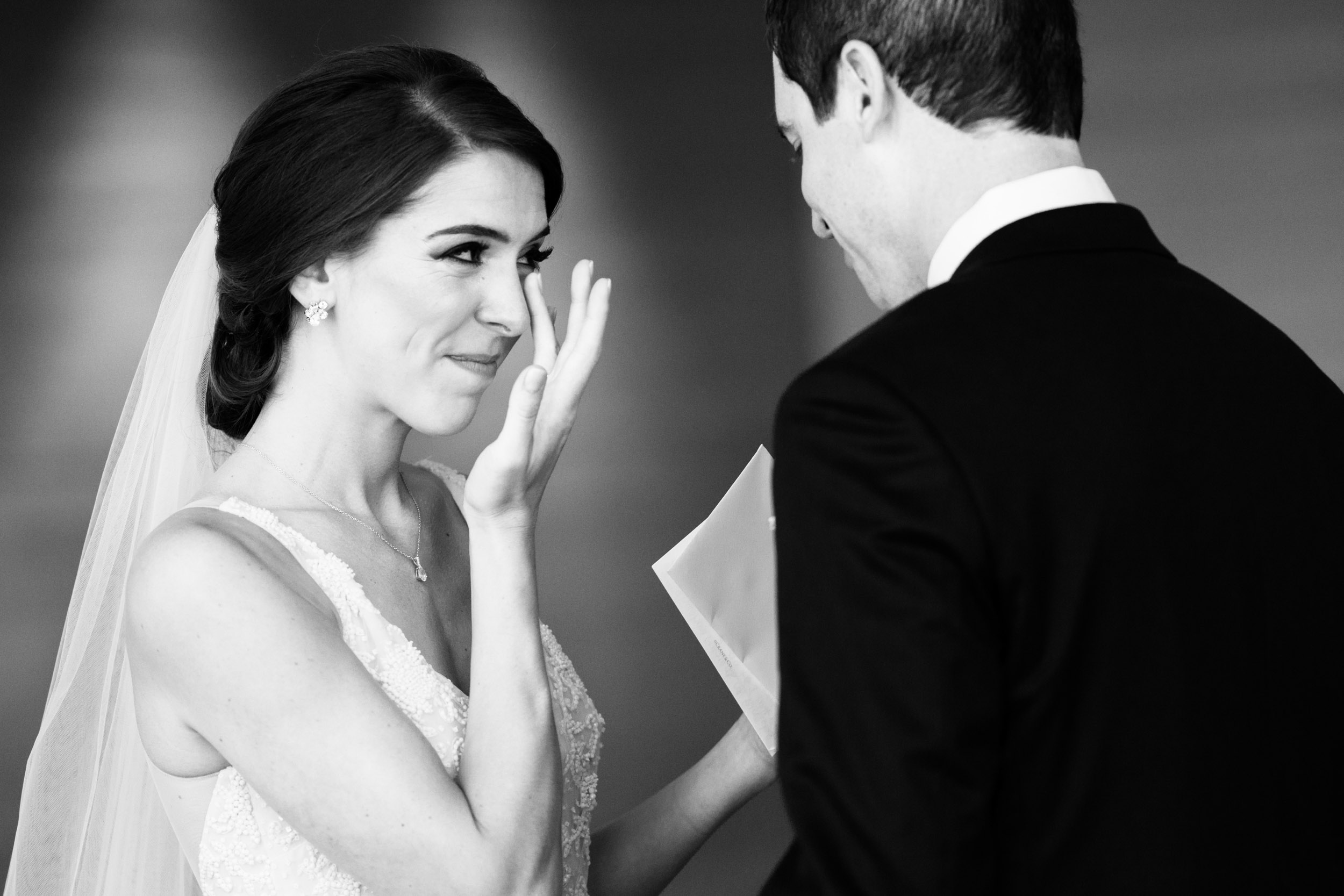 This is a beautiful photo of the bride wiping away tears during the first look at the Sheraton Grand in Chicago before a wedding at the Harold Washington Library.