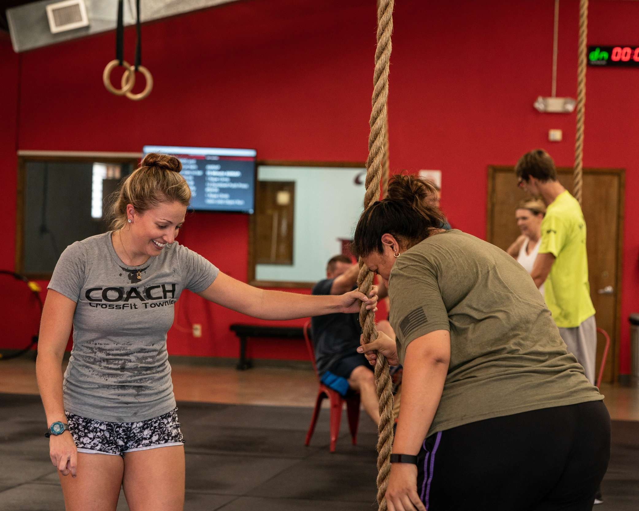 Coach Kelly Ledger shows Martha Millard how to do a rope climb