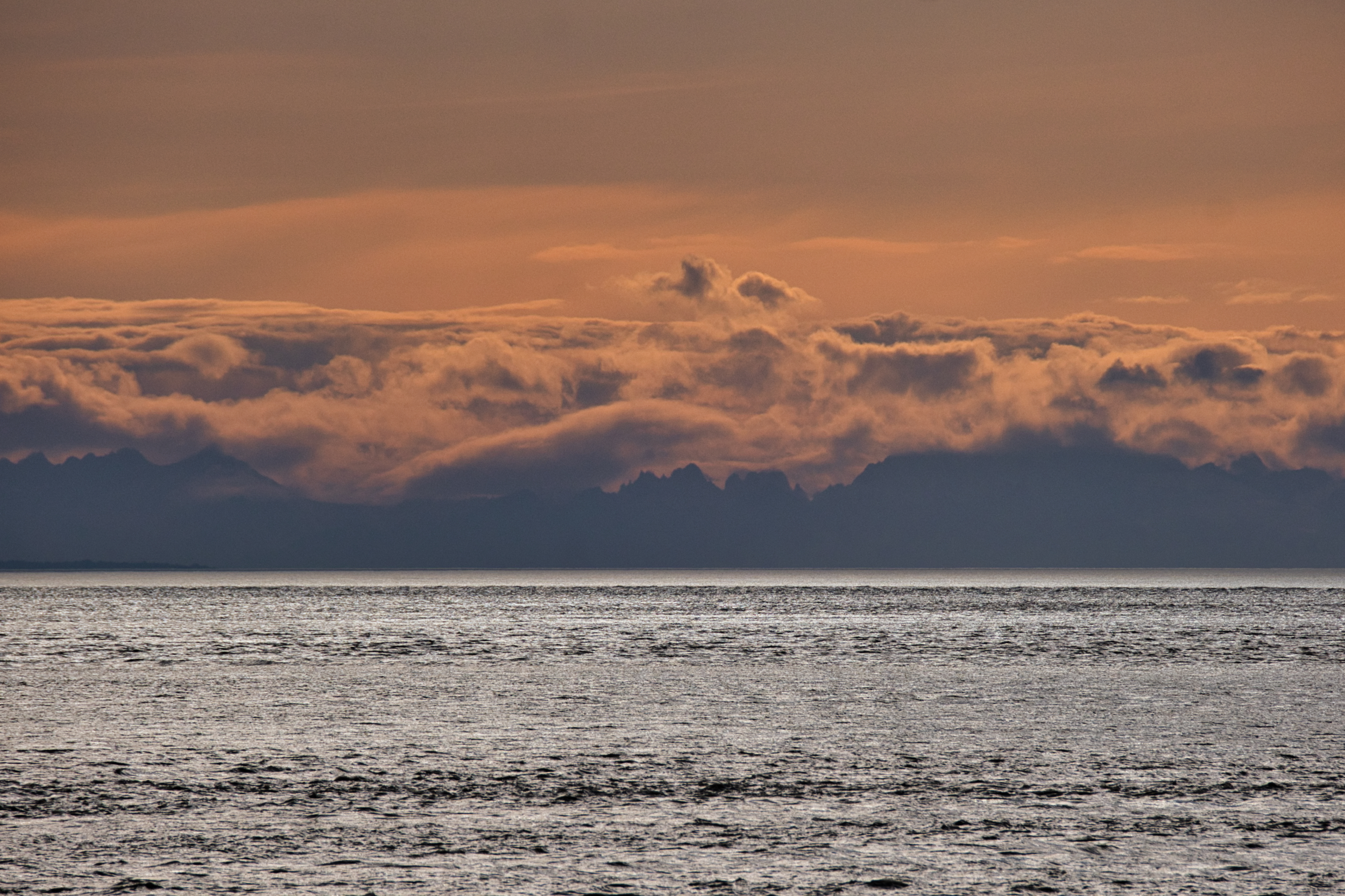 Cloud banks and faint mountains across Cook Inlet from Anchorage