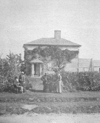 A photo ca. 1888 of the New House with outbuildings visible to the right.