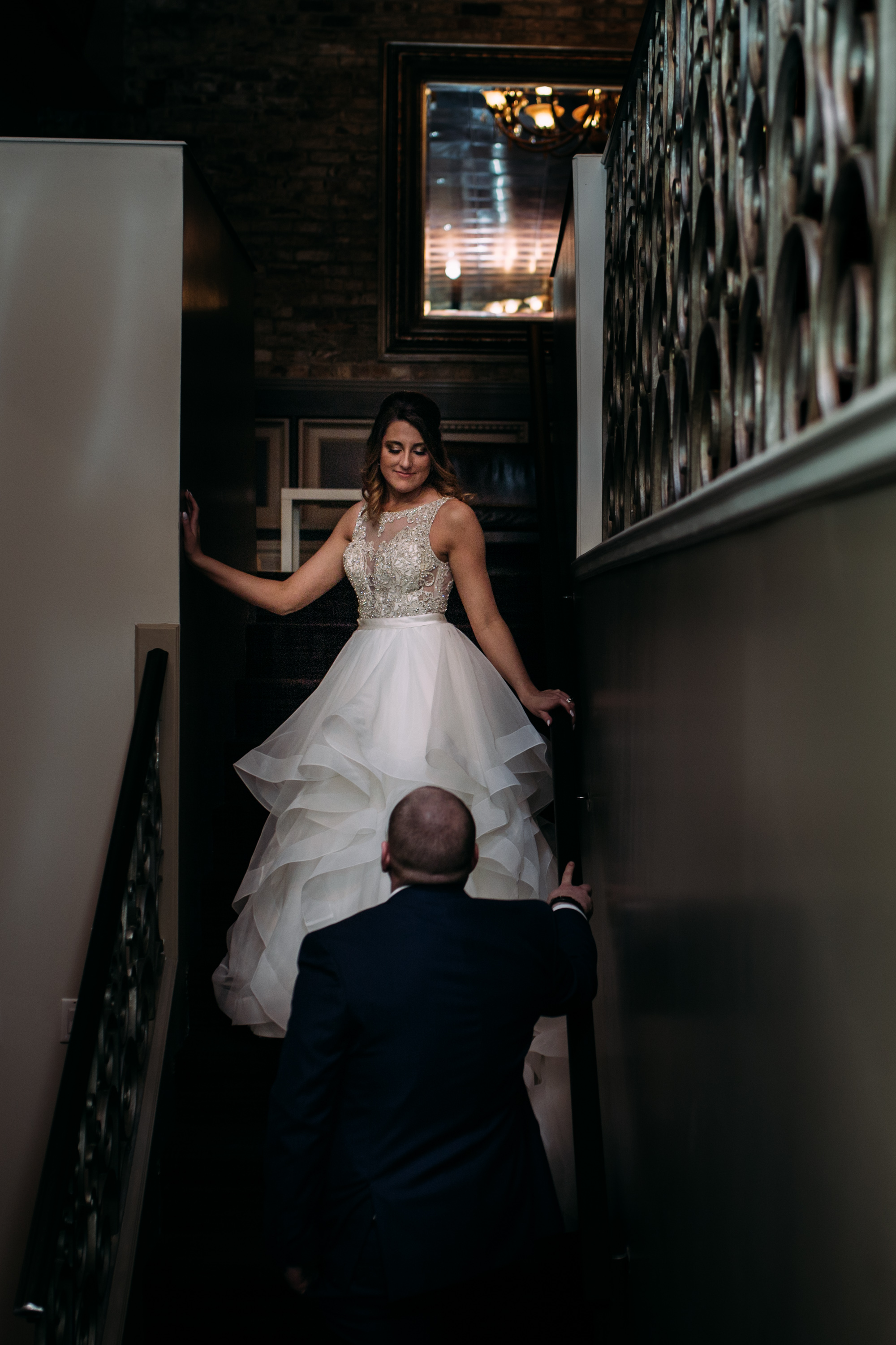 bride walks down the stairs towards her husband