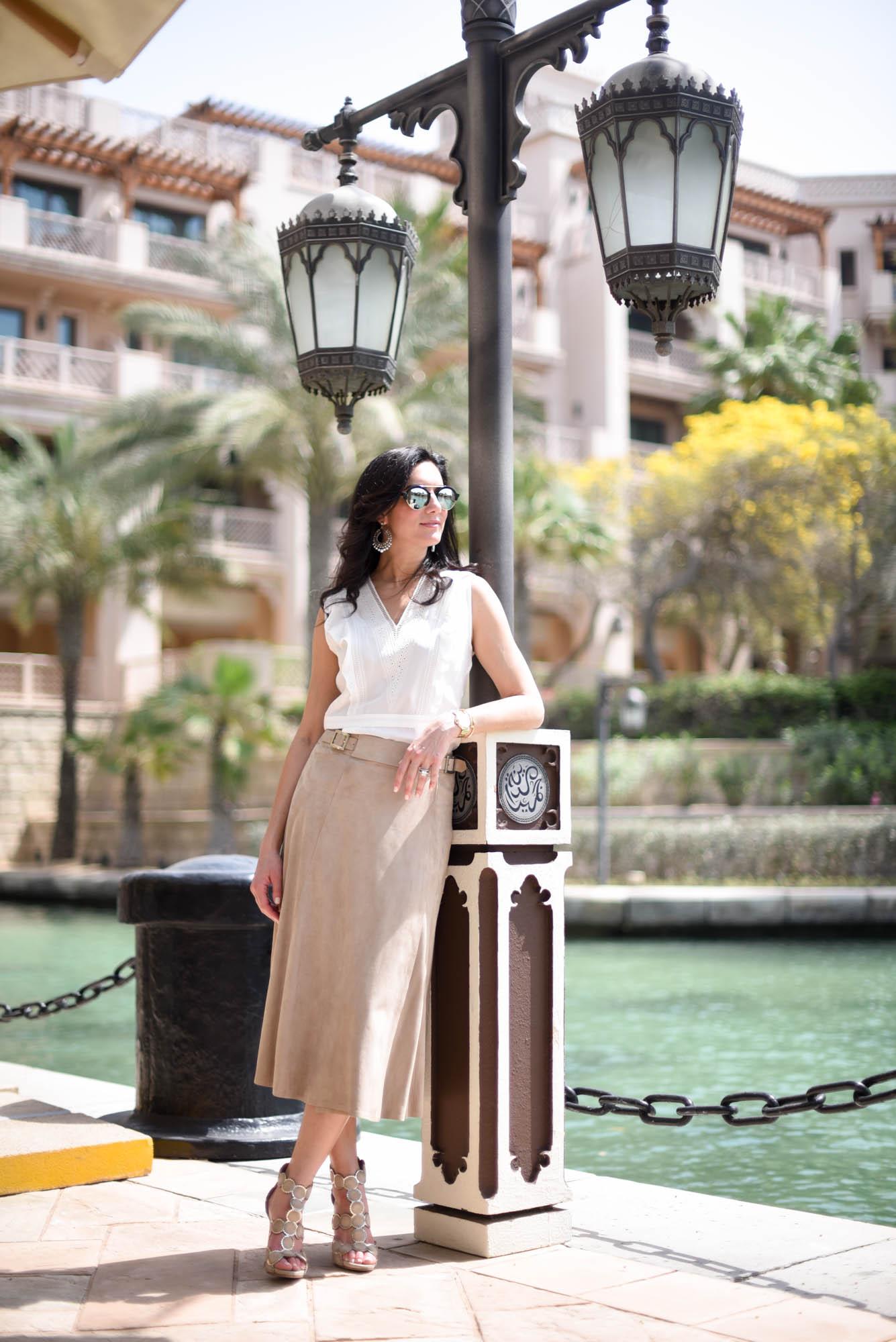 Wearing a Veronica Beard silk blouse, Ralph Lauren suede wrap skirt and Alaia heels
