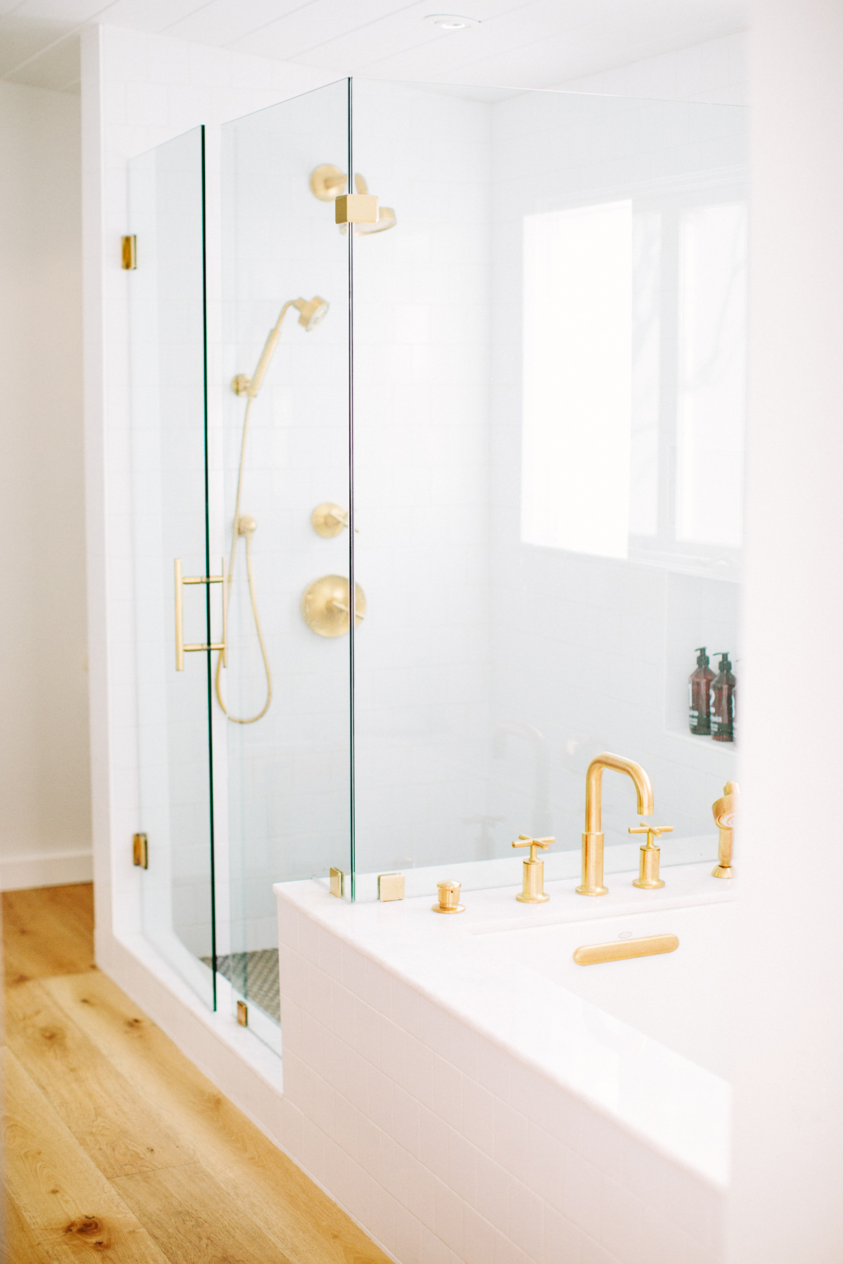 White, modern master bathroom shower design by Carly Waters Style