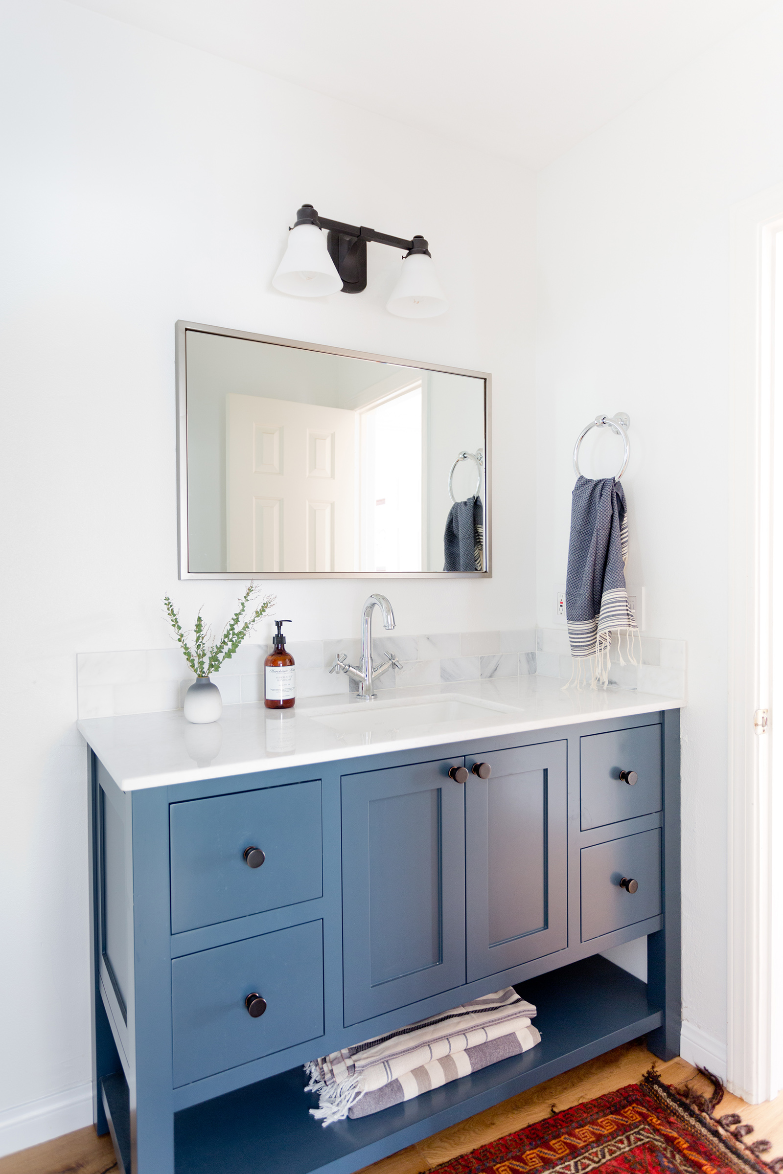 Modern bathroom with navy vanity design by Carly Waters Style