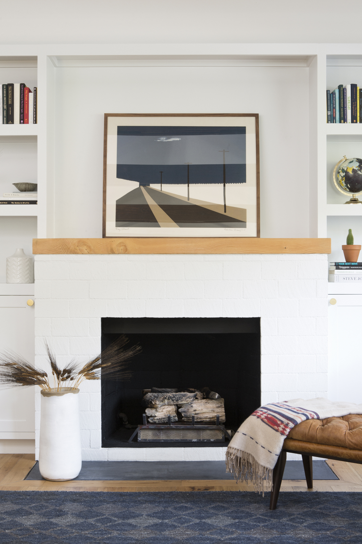 White fireplace with wood design by Carly Waters Style