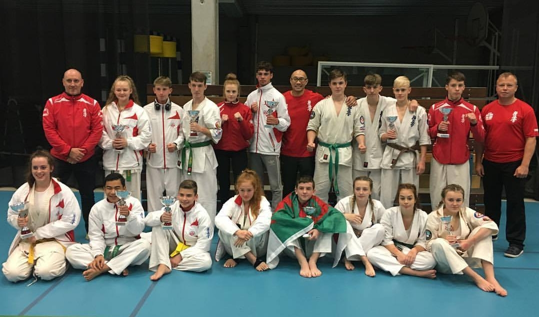 Teams England and Wales  BACK ROW (L to R)  Sensei Chris Davies (Wales coach), Maise Blackford (Eng), Luke Sabey (Eng), Luke Jones (Wales), Sophie Hobbs (Wales), Ame Sorge (Eng), Sensei Wai Cheung (Eng coach), Rob Salvi (Eng), Aaron Sheehan (Wales), Luke Davies (Wales), Max Williams (Wales), Sensei Tony White (Eng coach)  FRONT ROW (L to R)  Beth Salvi (Eng), Bart Proctor (Eng), Dennis Sorokins (Eng), Jessica Charsley (Eng), Rhys Meredith (Wales), Holly Harvey (Wales), Lili Bryan (Wales), Mia Morgan (Wales)