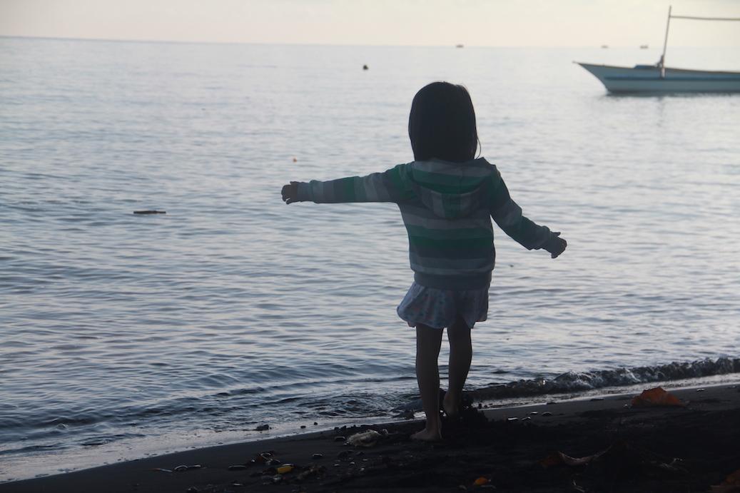 Balinese girl playing on Bali Sea shore
