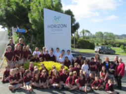 The students around our newly renamed and rebranded sign.