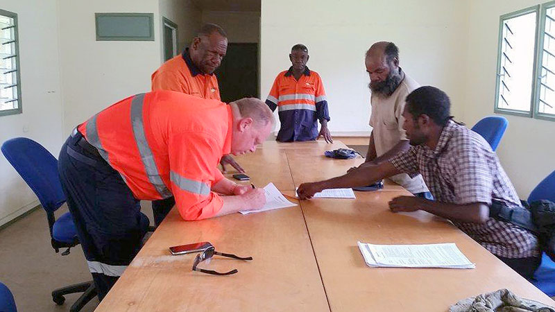 Mr Richards signing the Contract and DTS Directors' Kisip Sakarias and Casper Yumbe look on. Witnessing the signing were WGJV community affairs officers.