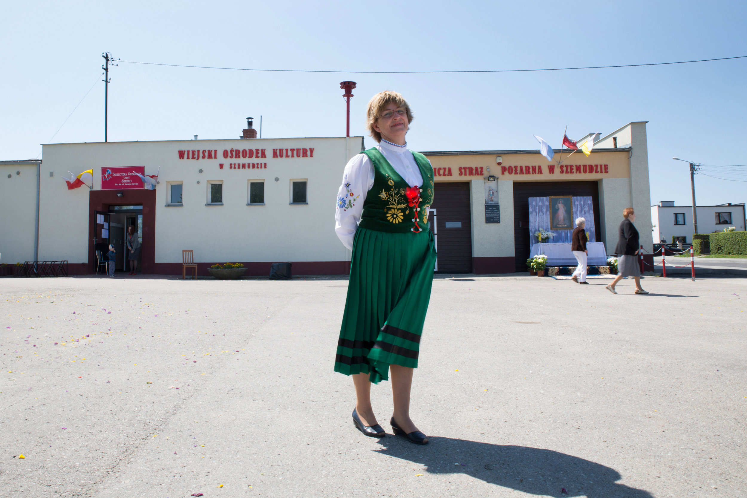 A woman wearing a traditional Kashubian outfit waits to join a religious procession in Szemud.