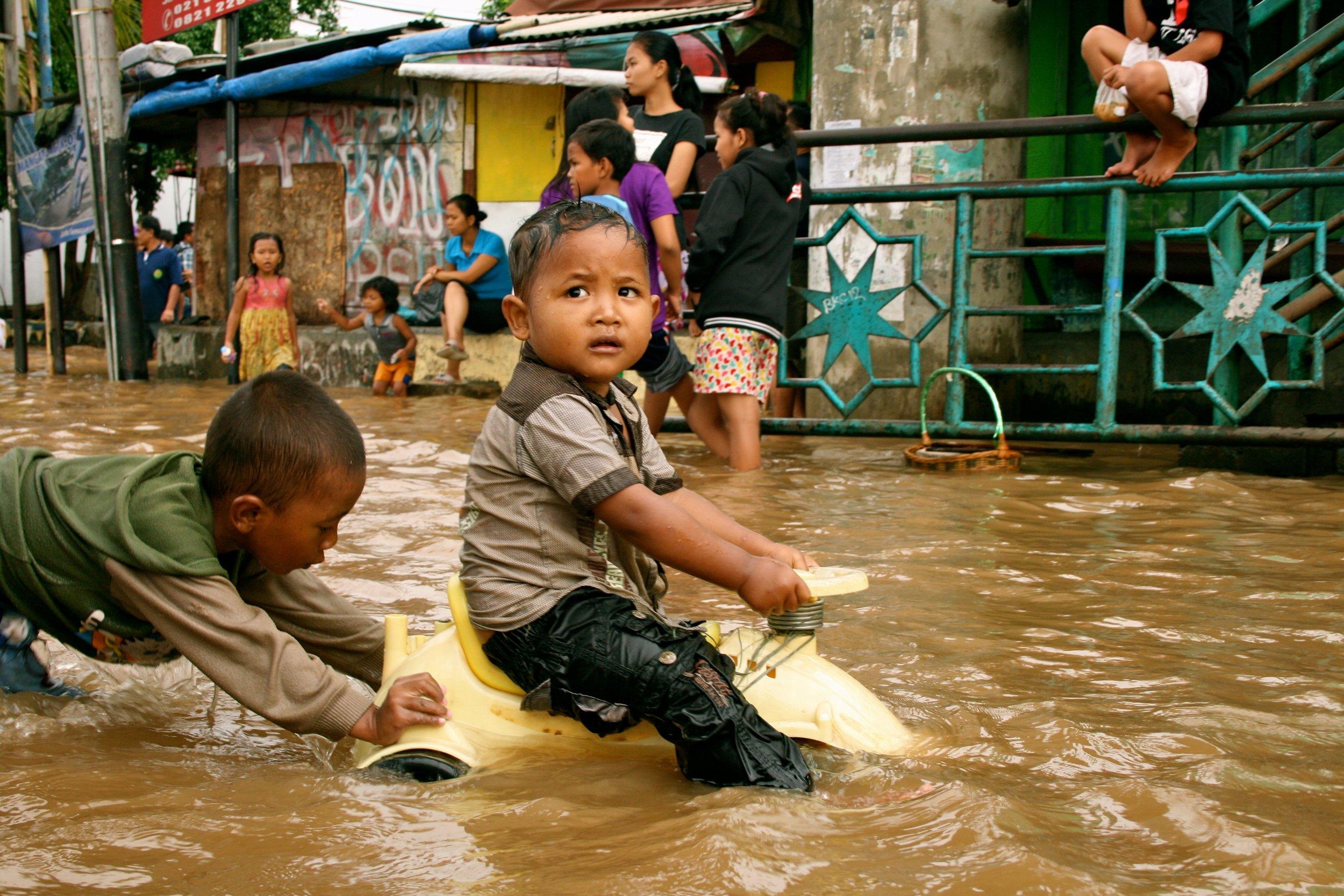 Children play in flood waters after torrential rains in Kampung Melayu, Jakarta. Photo by Kate Lamb, Freelance journalist