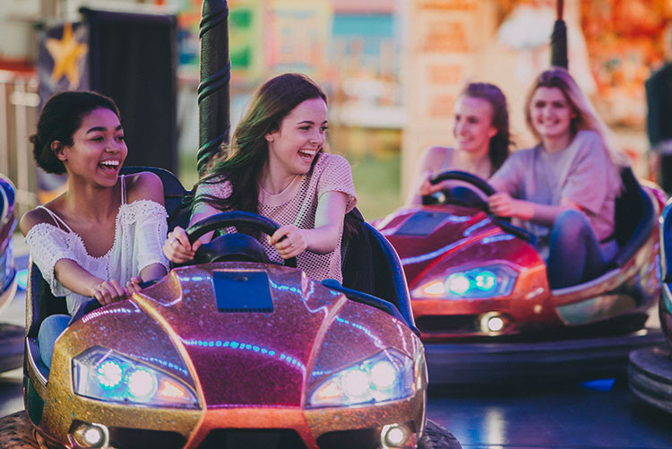 Laughing young girls playing bumper cars