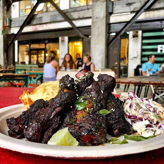 """Tamarind Glazed Spare Ribs might not be what comes to mind when you think """"Indian street-food,"""" after all — there's not a lot of pork found in Indian dishes. But Meherwan LOVES ribs, as do southerns. So, actually, it would be pretty weird if we didn't have ribs on the menu…right? 🤙🏽  Inspired by Desi-Chinese cuisine, @MeherwanIrani found a way to sneak one of his faves onto the Botiwalla menu — asian styled ribs, but w/ an Indian twist. India and China's close proximity led to a cuisine that's not quite Indian but not completely Chinese. It's the Indian equivalent of Tex-Mex. And it's delicious. Think, soy sauce meets garam masala, scallions meet cilantro, and tamarind mixing it up with szechuan. Our recipe is a blend of what Desi-Chinese tastes like to Meherwan — salty, sweet, and sour ribs braised in cinnamon, stars anise, tamarind, soy, lots of black pepper, jaggery (brown sugar), garlic, and ginger. After braising for an hour, we reduce the braising liquid and add lots of tamarind and chaat masala. Made to order - the ribs are crisped the in the fryer and then tossed in the tamarind-ginger glaze and dusted w/ toasted sesame seeds and scallions. Available at both our @poncecitymarket & Alpharetta locations....we'll see you soon tho @optimisthallclt 😘 Thanks for the tasty pic @charlotteagenda! 💛"""