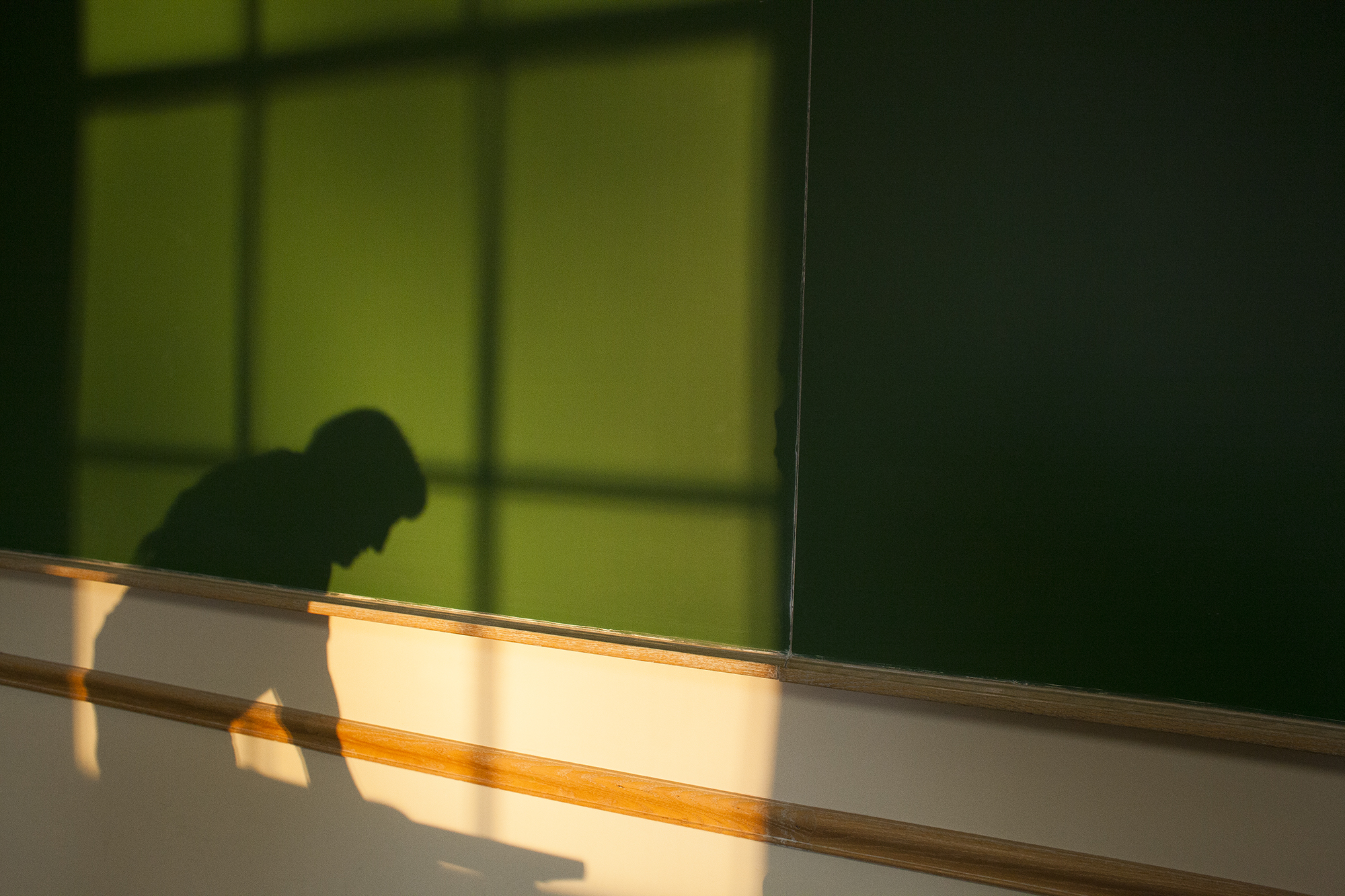 A custodian cleans a classroom at sunset. (Babz Jewell 2017, all rights reserved)