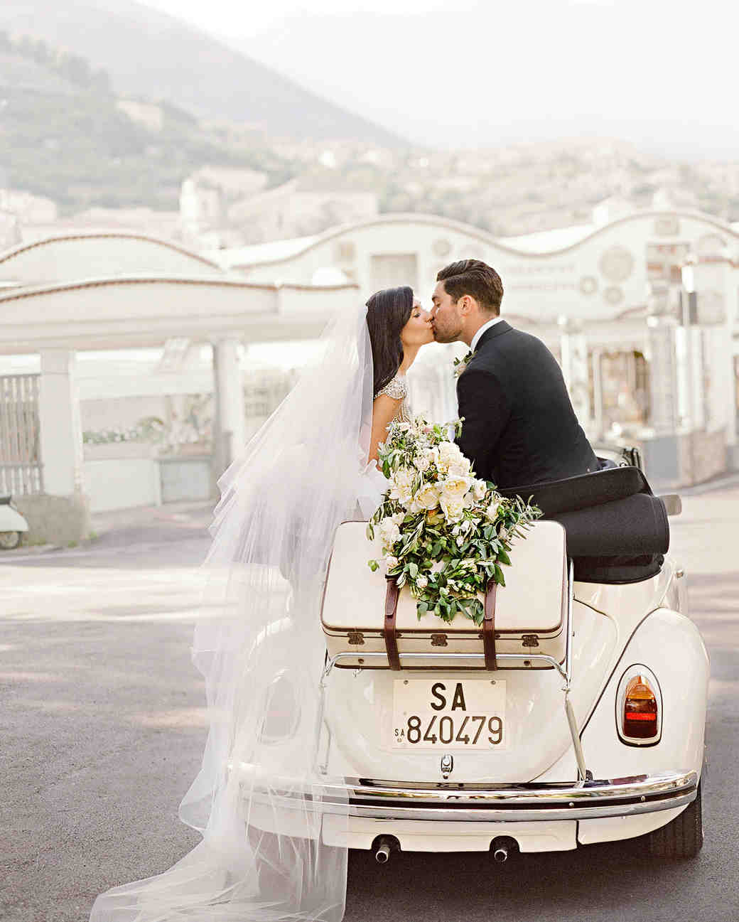 couple-wedding-kissing-car-italy-103351309_vert.jpg