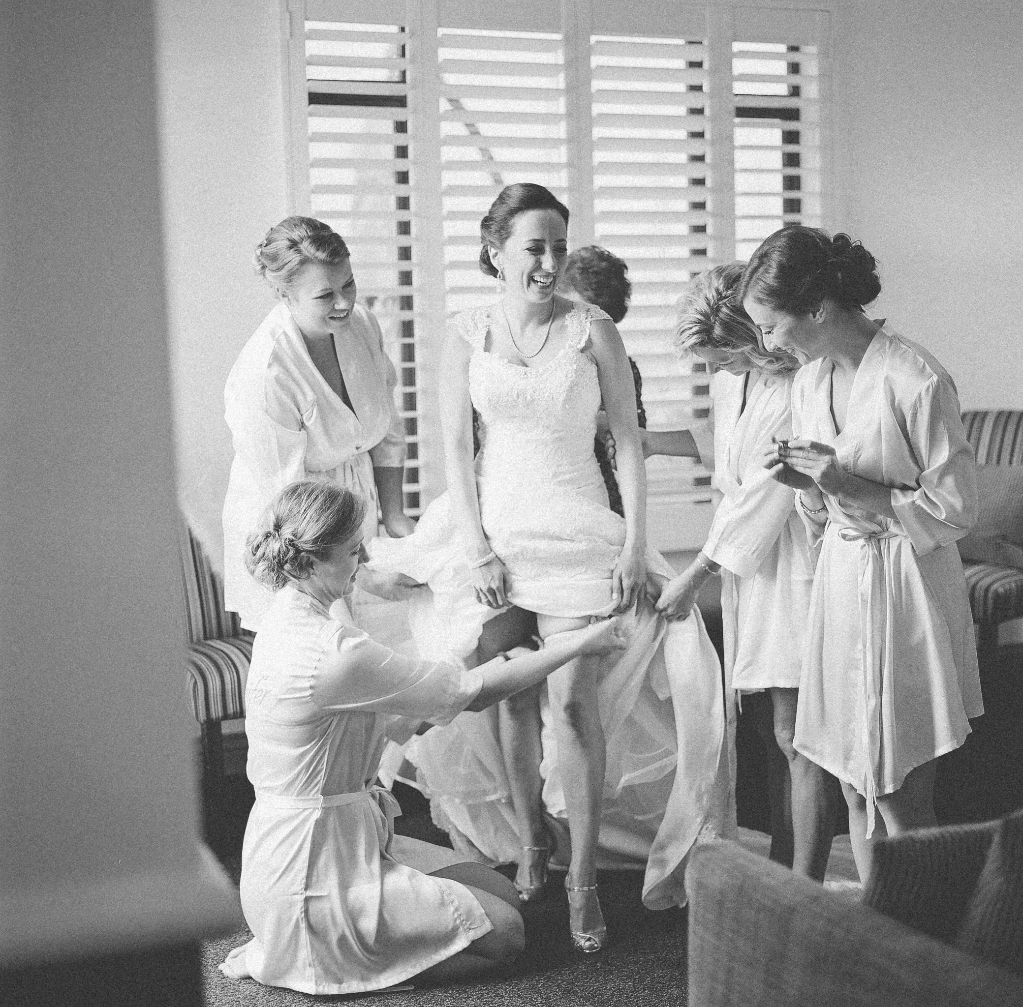 the bridesmaids all helping the bride get dressed!
