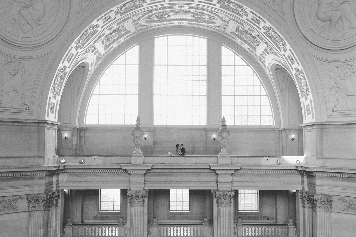The bride and groom kiss on the 4th floor balcony, under the dramatic arch of San Francisco City Hall.