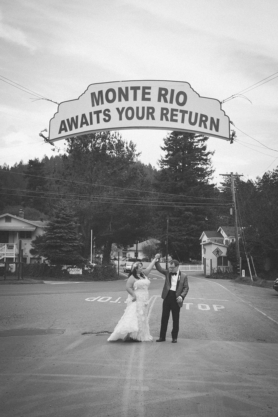"The groom twirls the bride in Monte Rio, underneath the famous, ""Monte Rio Awaits Your Return"" sign."