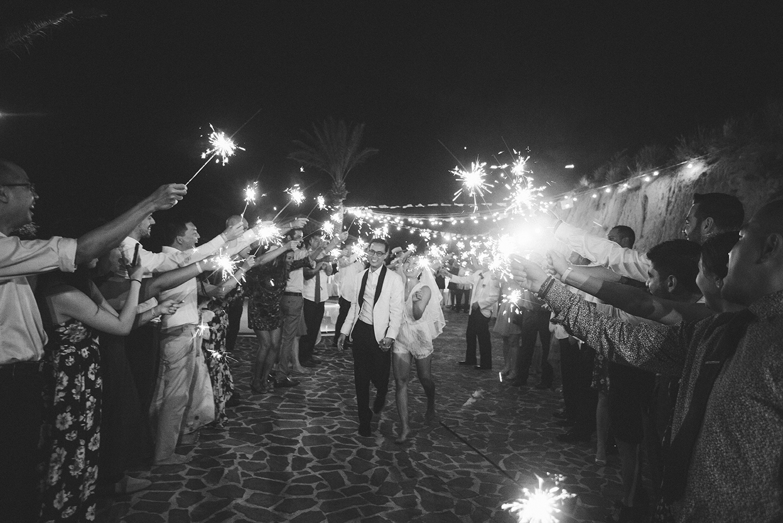 Bride and groom run through a sparkler exit at Pueblo Bonito Sunset Beach resort.