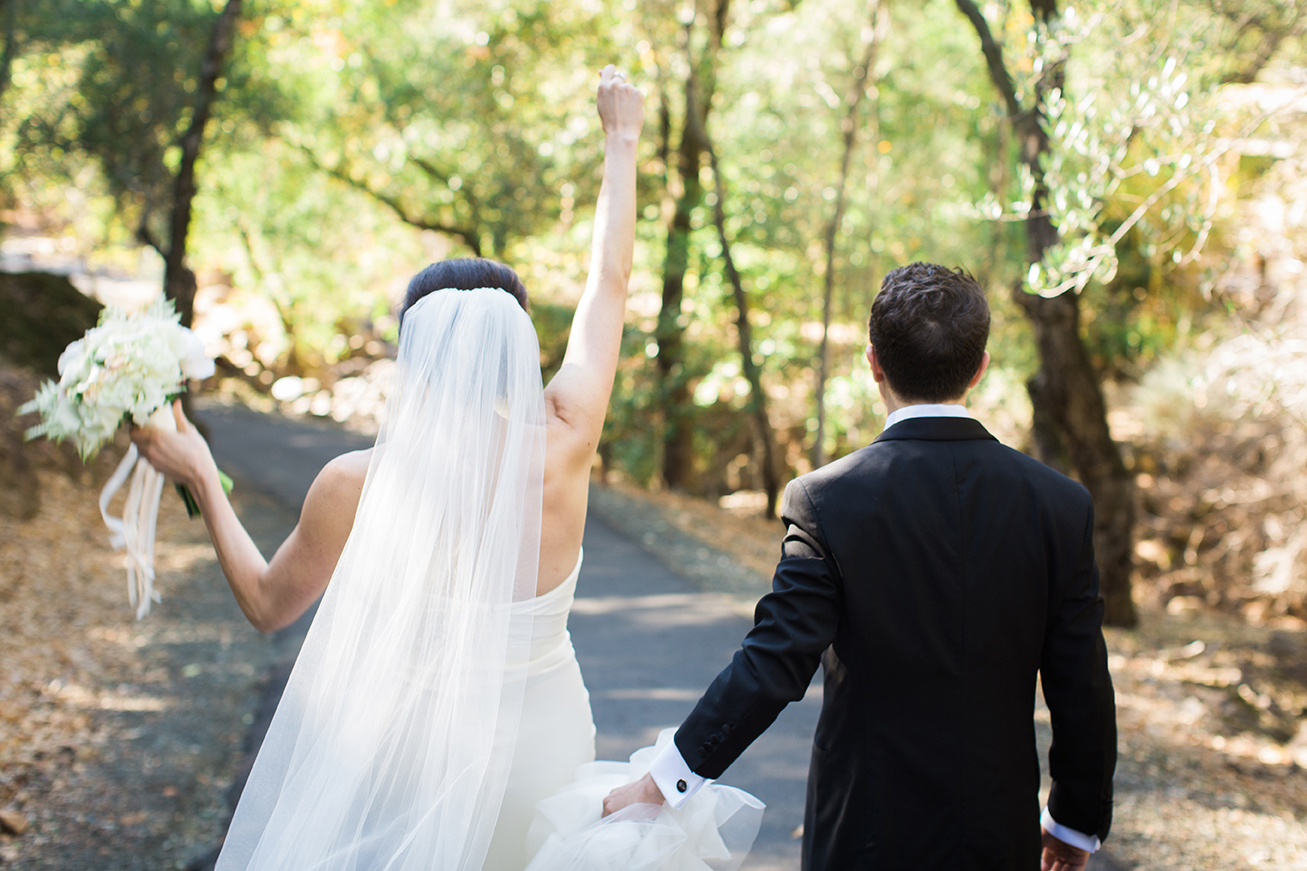 Bride punches her fist in the air in celebration while groom holds her dress at Auberge du Soleil.