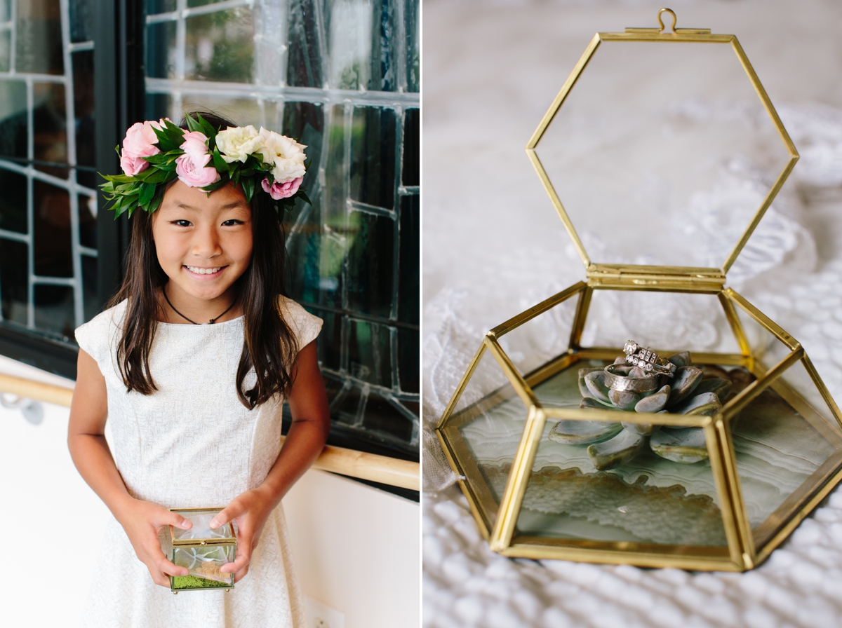 A smiling flower girl hold the glass ring box, while wearing a flower crown.