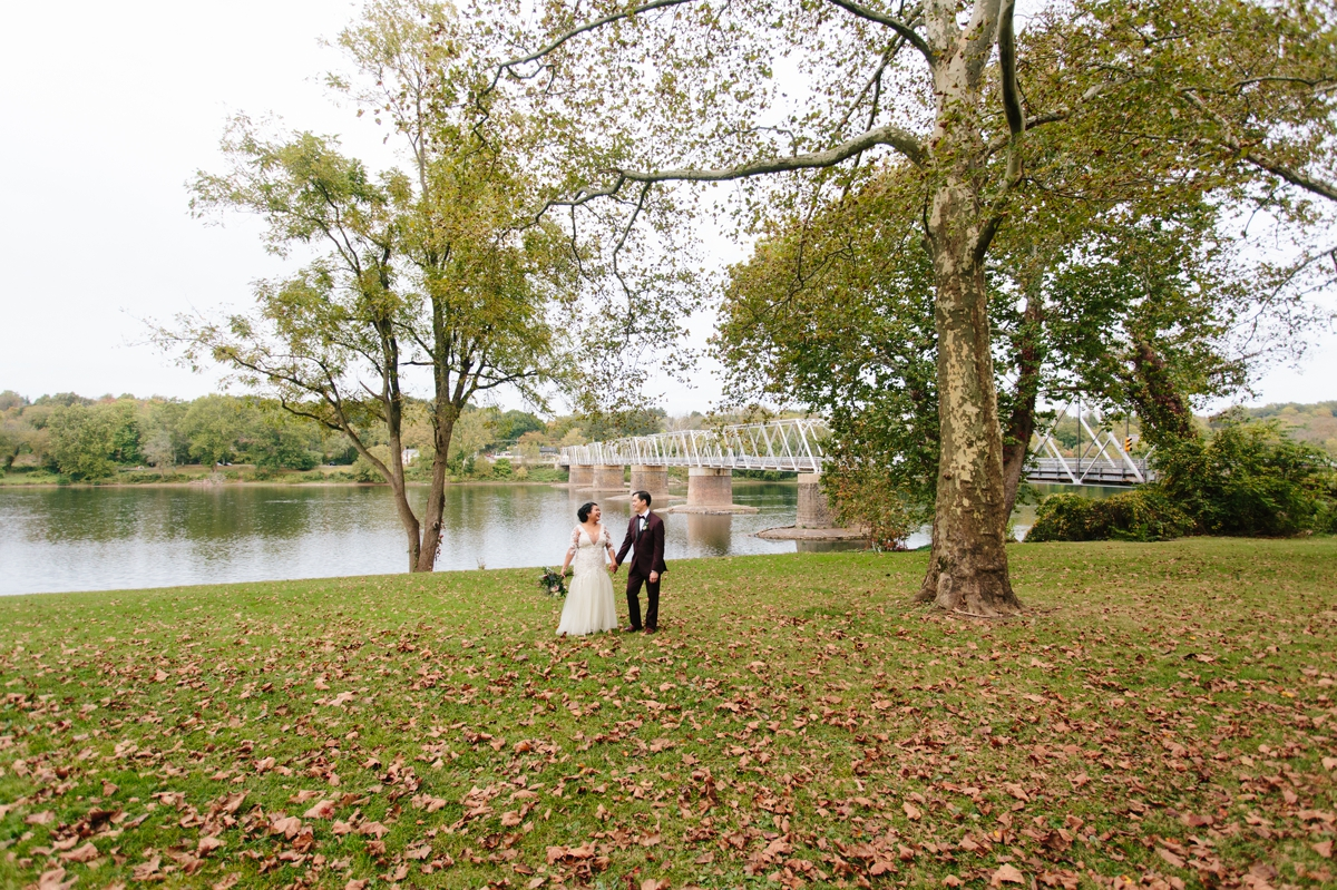 The bride and groom stroll through the fall leaves by the Delaware river at Washington Crossing Park.