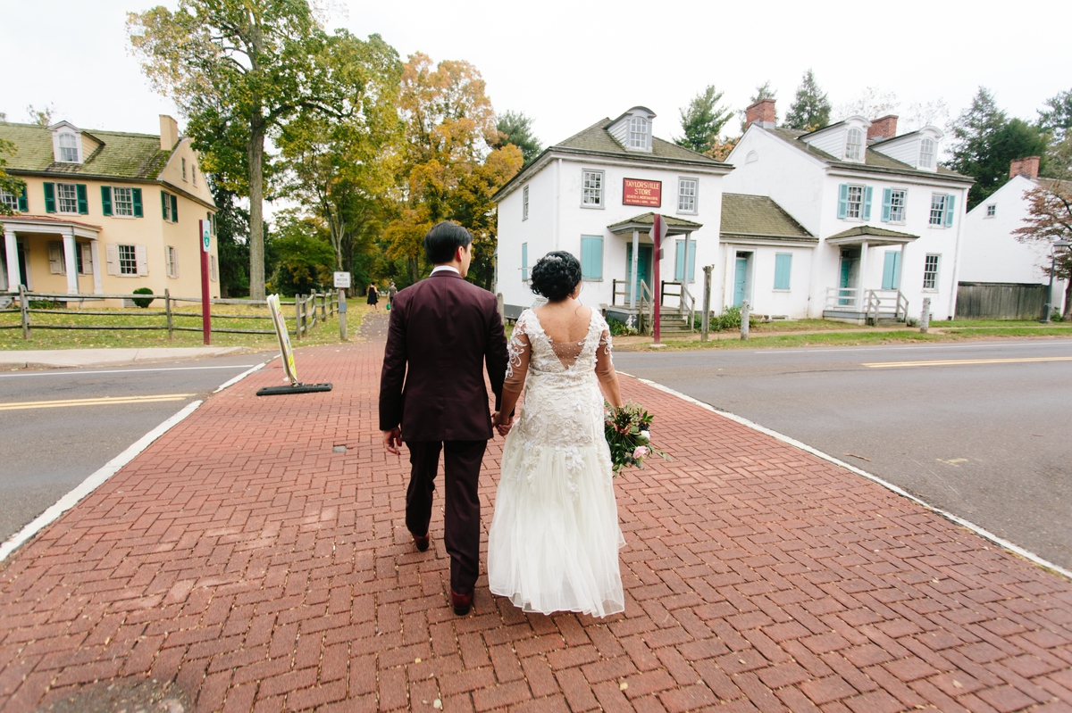 The groom and bride cross the street through the historic buildings at Washington Crossing Park.
