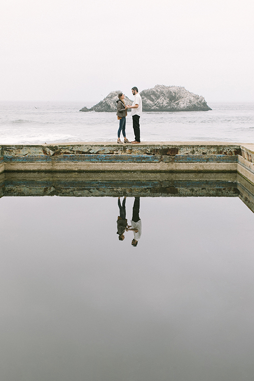The engaged couples' reflection in the water at Sutro Baths, with Seal Rocks in the background.