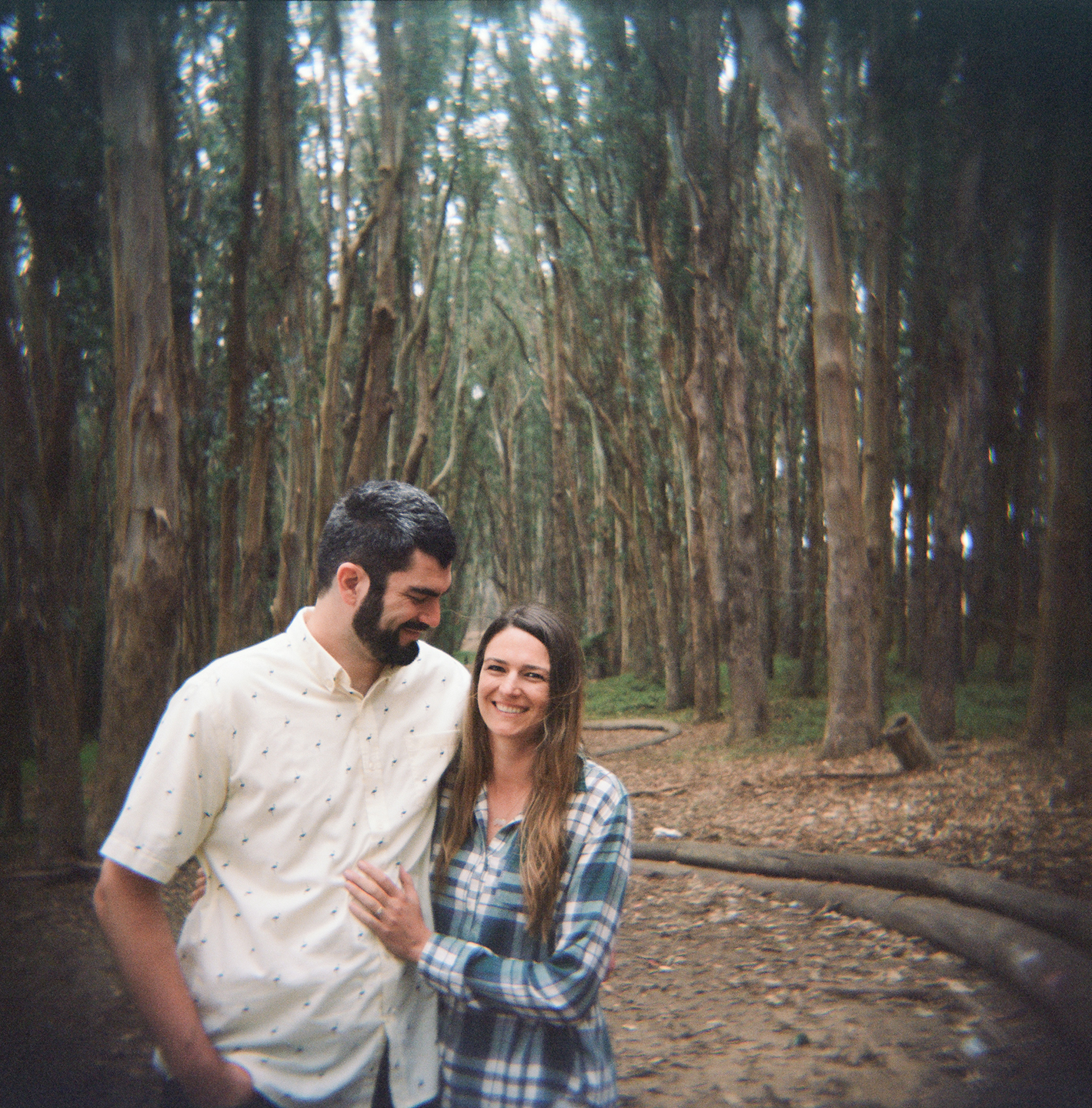 A happy engaged couple in the Presidio of San Francisco.